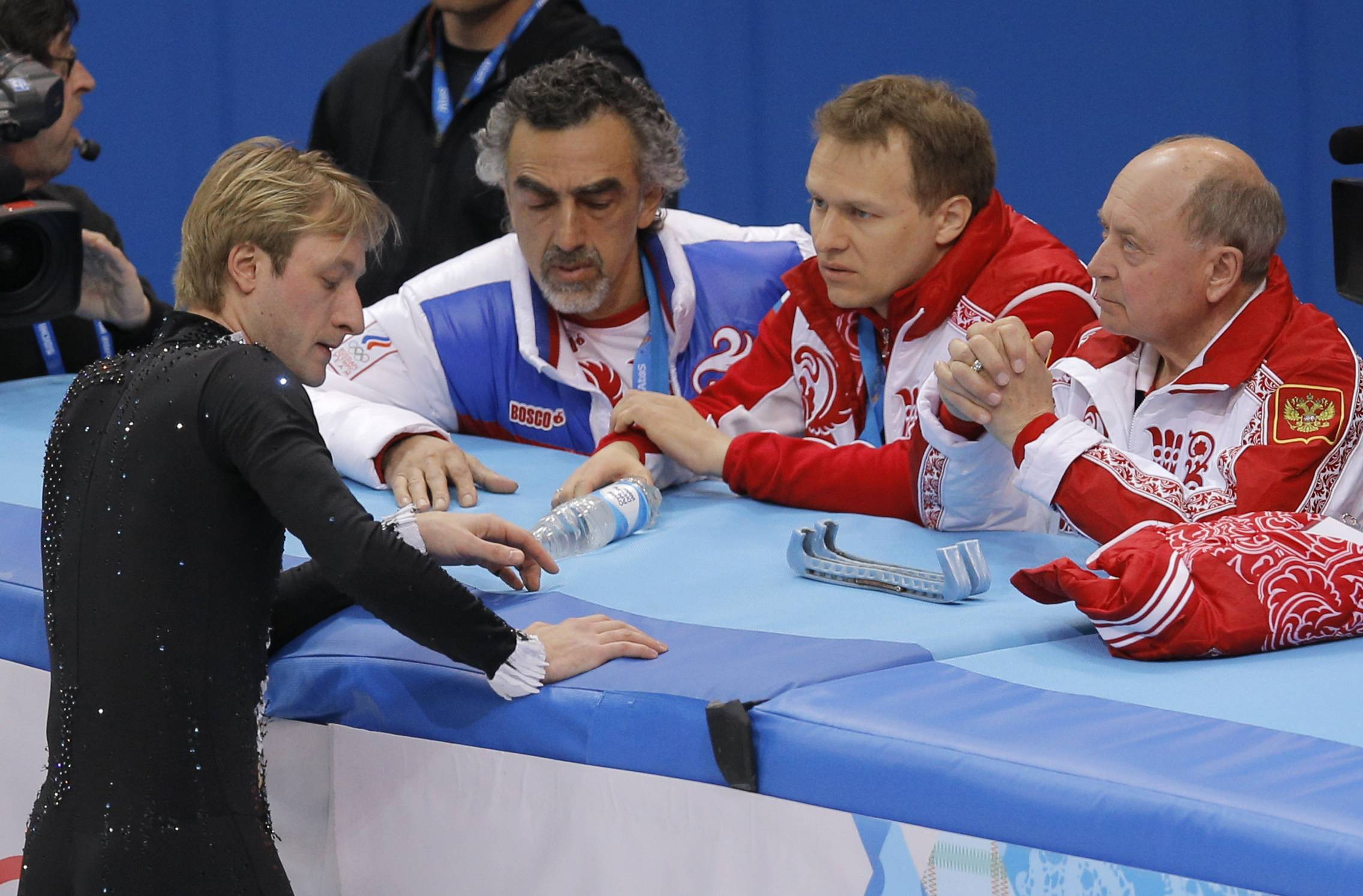 Evgeni Plushenko of Russia, left, speaks with team members, including his coach Alexei Mishin, right, before he pulled out of the men's short program figure skating competition due to illness at the Iceberg Skating Palace during the 2014 Winter Olympics, Thursday, Feb. 13, 2014, in Sochi, Russia.