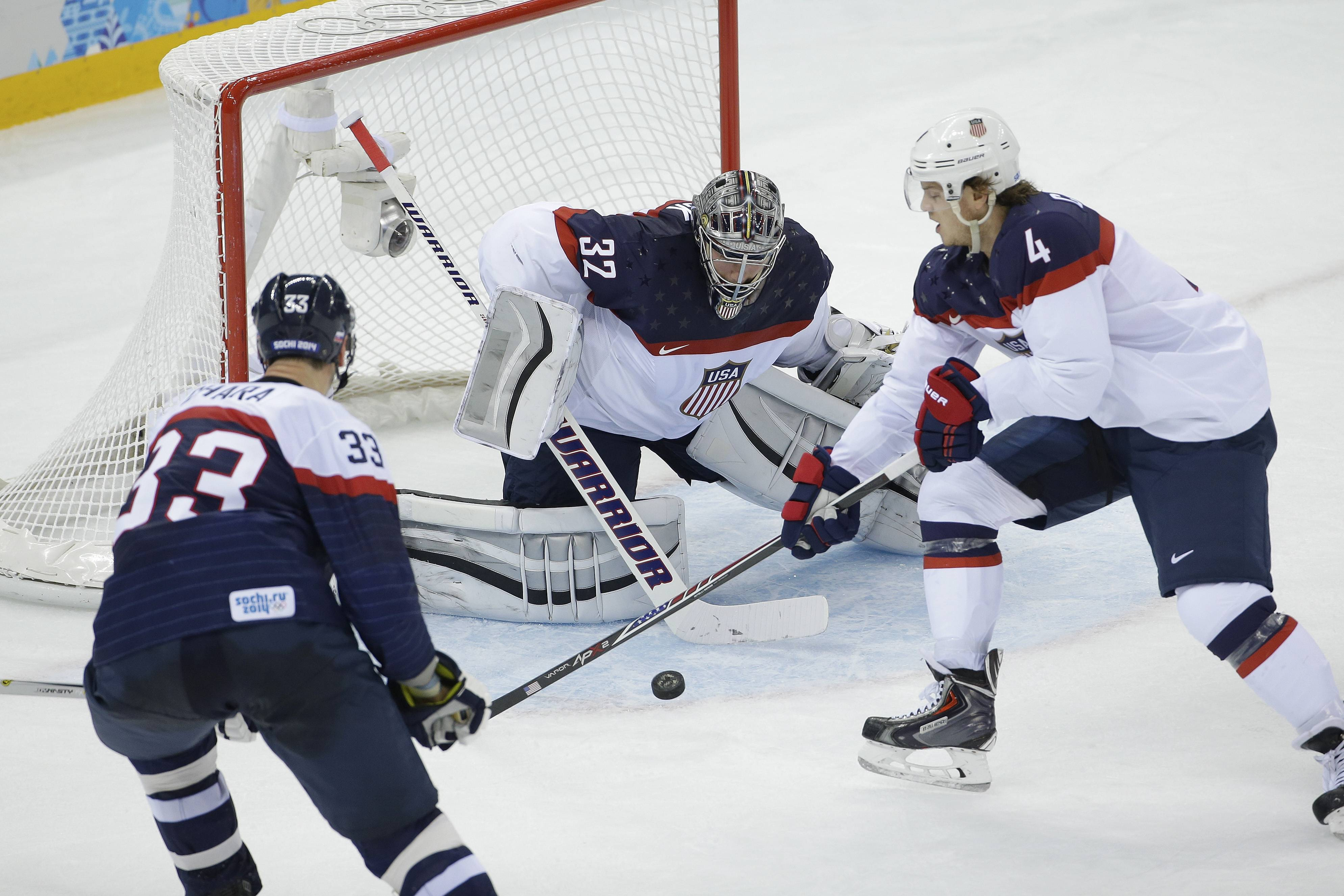 USA goaltender Jonathan Quick and defenseman John Carlson (4) defend against Slovakia defenseman Zdeno Chara (33) during the 2014 Winter Olympics men's ice hockey game at Shayba Arena, Thursday, Feb. 13, 2014, in Sochi, Russia. USA defeated Slovakia 7-1.