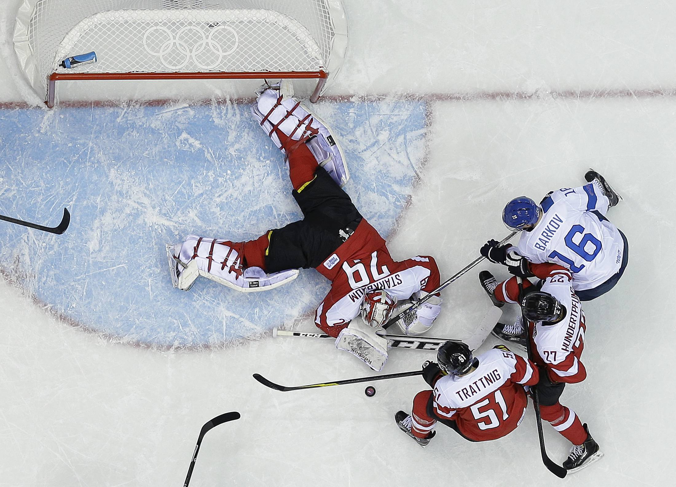 Austria goaltender Bernhard Starkbaum reaches for the rebound as Finland forward Aleksander Barkov looks to score Thursday in the third period at the 2014 Winter Olympics in Sochi, Russia.