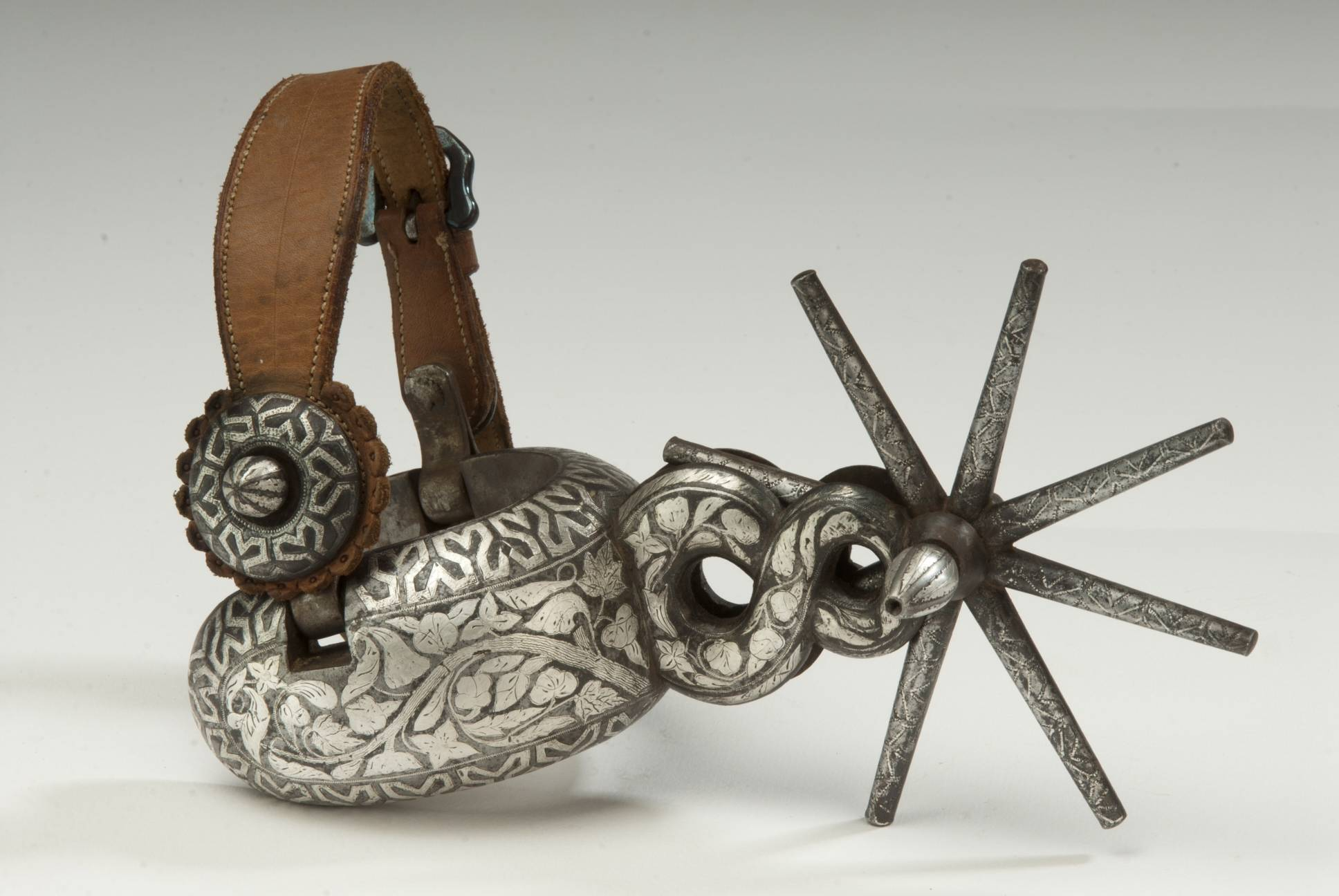 "A silver inlaid spur is on display at the Albuquerque Museum as part of the exhibition ""Arte en la Charreria: The Artisanship of Mexican Equestrian Culture."" Each item reflects different elements of the culture of the legendary charro, the Mexican horseman."