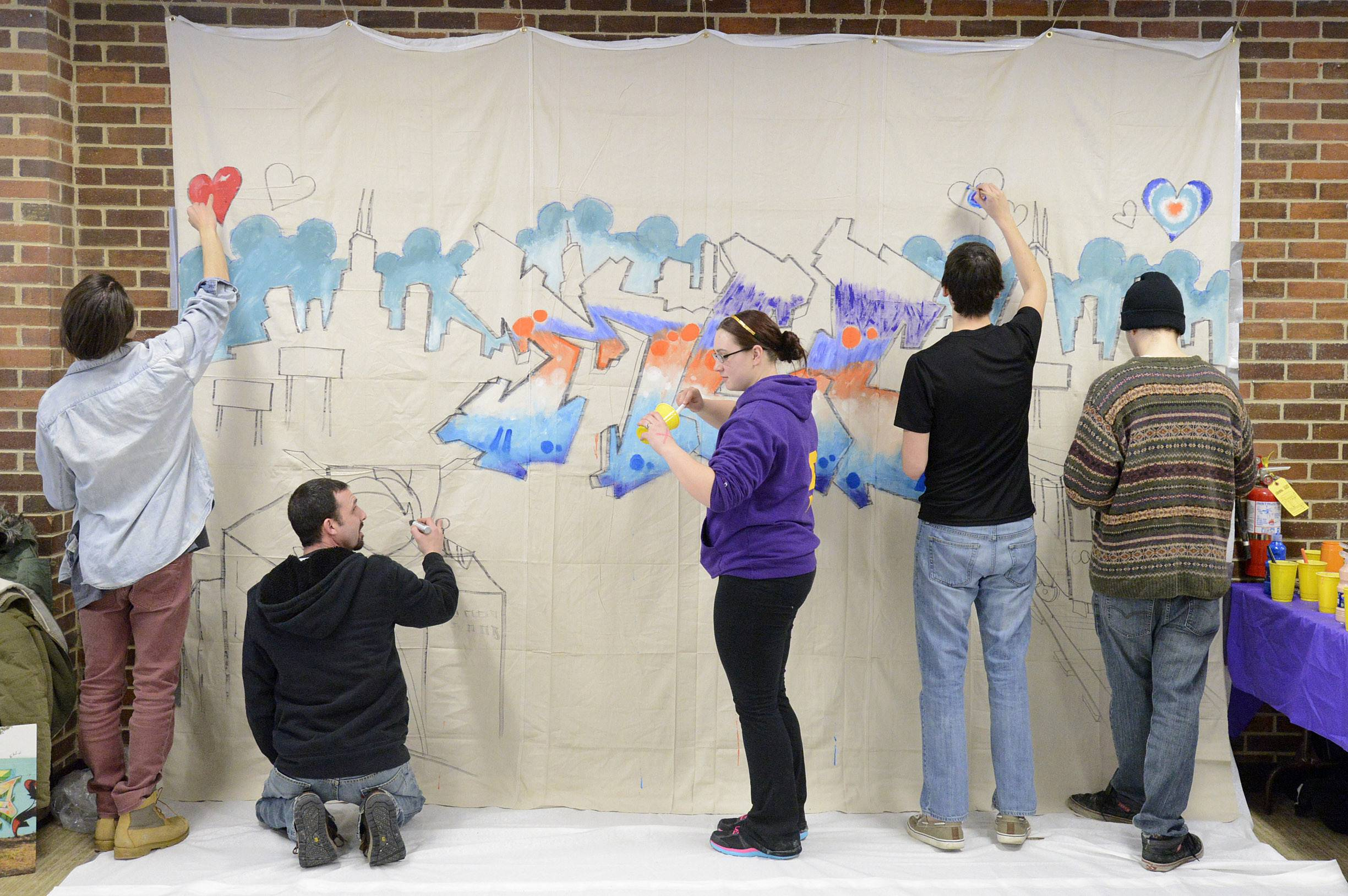 Students join artist Bill Weyna, second from left, fill in the graffiti-inspired mural Thursday at McHenry County College. Helping out, from left, are Ivan Burik of Crystal Lake, Weyna, Katie Barucca of McHenry, Erick Marchessault of Cary and Jake Kvidera of McHenry. Students helped with the mural between classes and during their lunch break.