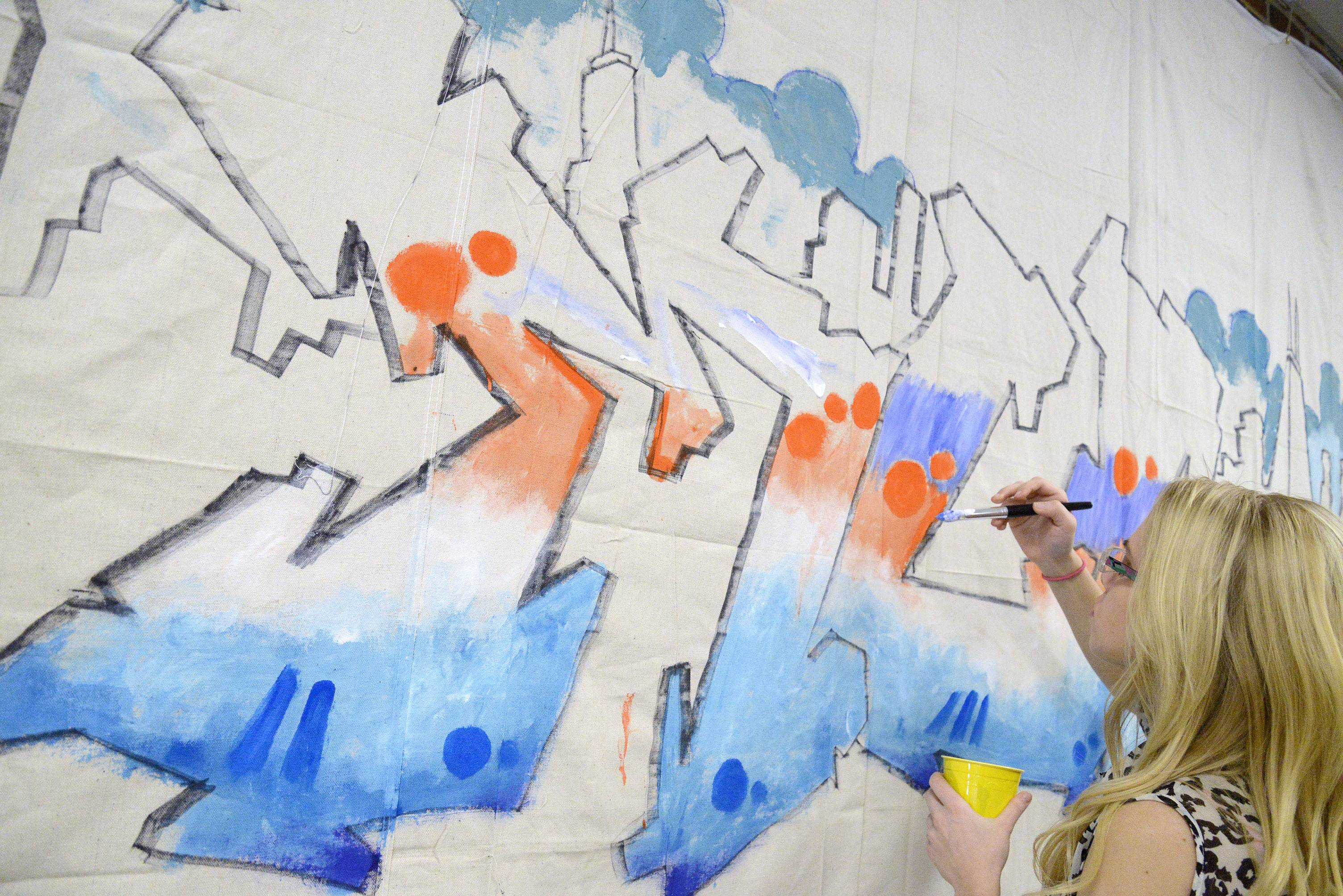 "McHenry County College student, Laurissa Mortensen, of Genoa City, Wis., paints in the letters ""MCC"" in the freestyle sketch by Chicago artist Nino Rodriguez of Chicago Thursday at the Crystal Lake campus."