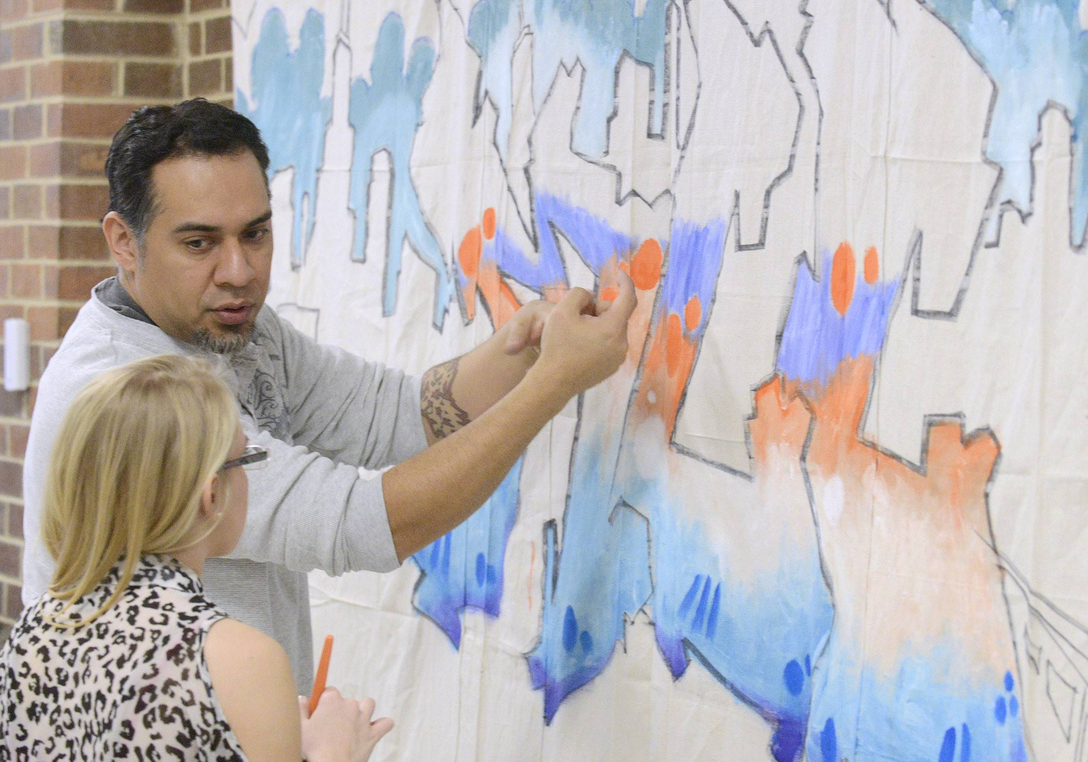 Chicago artist Nino Rodriguez gives McHenry County College student Laurissa Mortensen tips for painting on the graffiti-inspired mural he created Thursday. Rodriguez drew parts of the mural and students helped complete the painting.