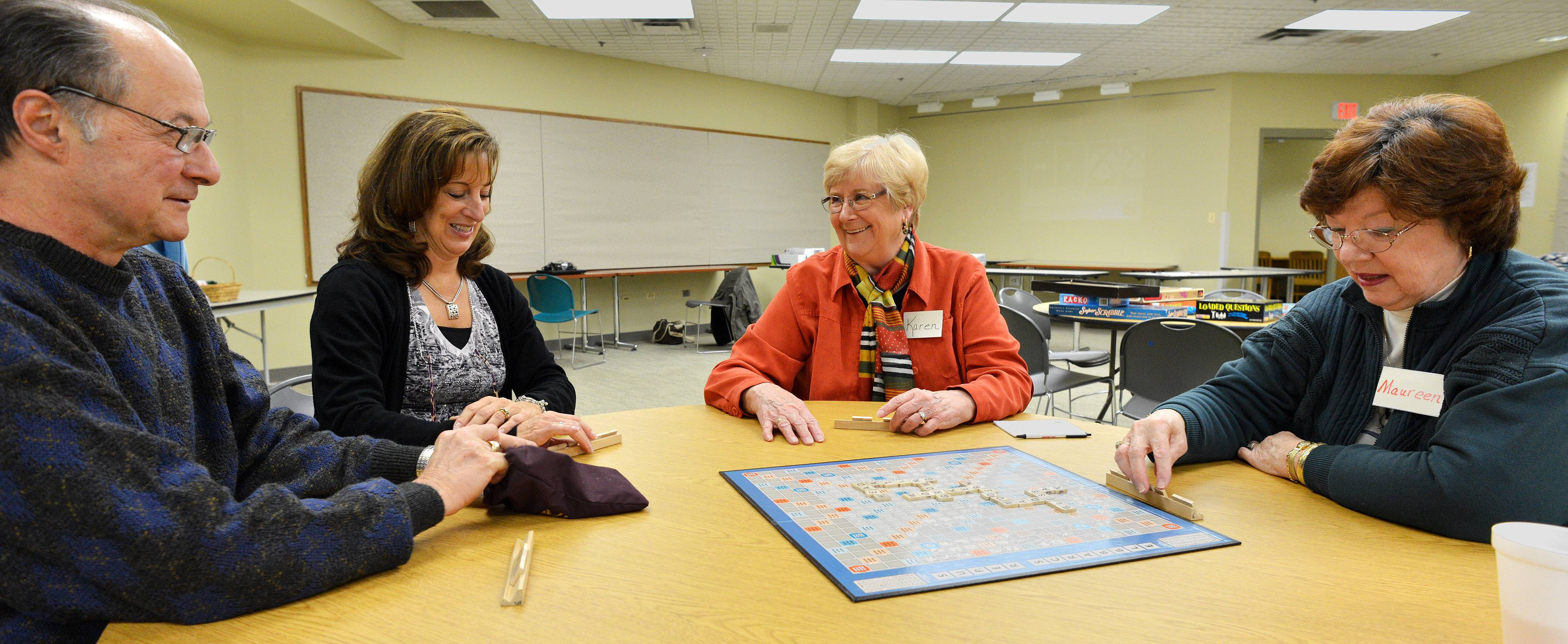 Super Scrabble is one of the more popular board games enjoyed by the senior citizens at the Bloomingdale Public Library's Senior Games. From left are Gene Carsello, Library Reference Assistant Brenda Levin, Karen Paras and Maureen Dolis.
