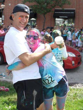 "Mark Rouse, owner of Runners High 'n Tri in Arlington Heights, with his daughter following the 2013 Color Run in Arlington Heights. Supports will hold a ""virtual run"" in Rouse's honor this weekend."