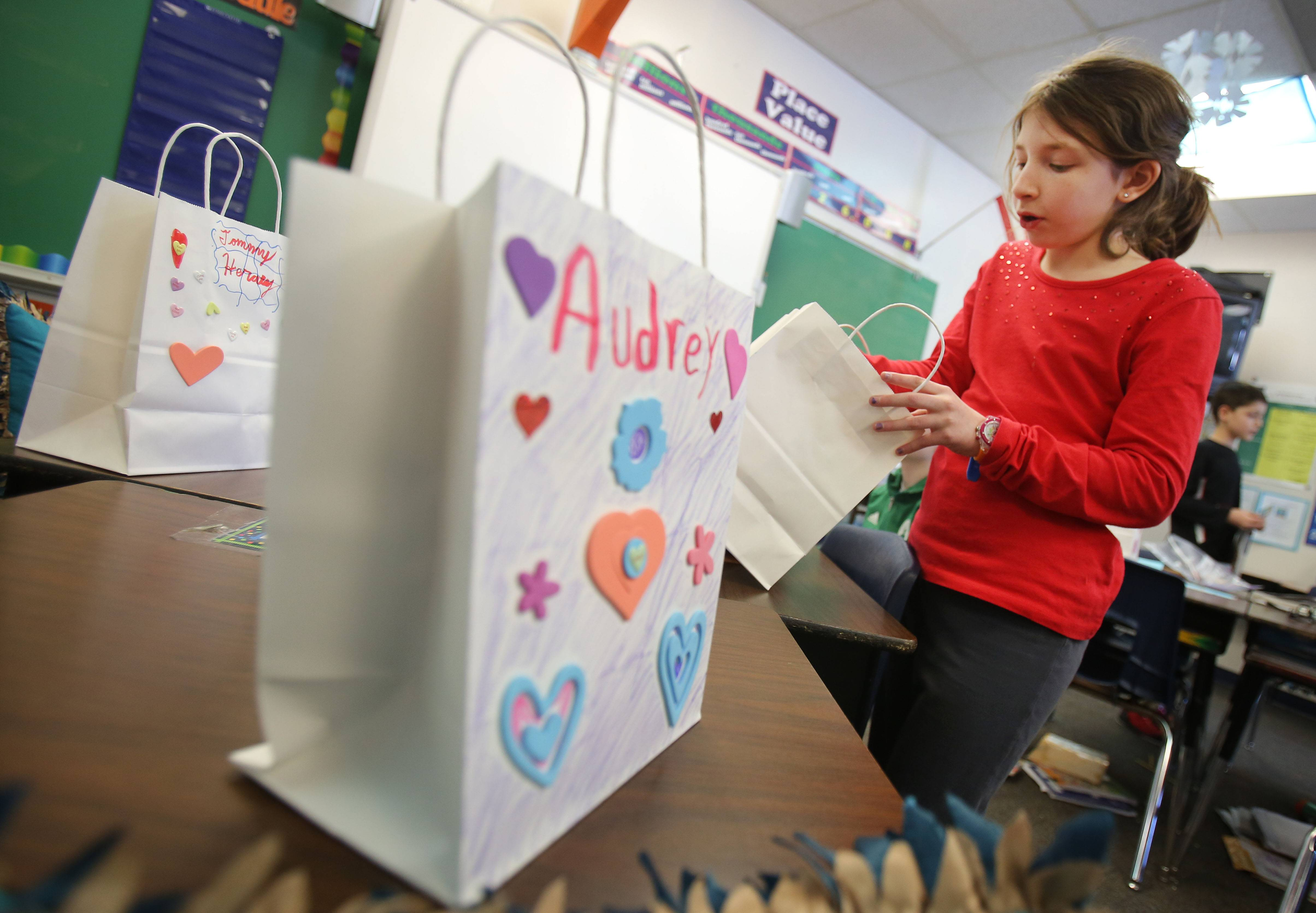 Forth-grader Megan Snow checks out the valentines she got from classmates during a Valentine's Day party at Butterfield School in Libertyville Thursday.