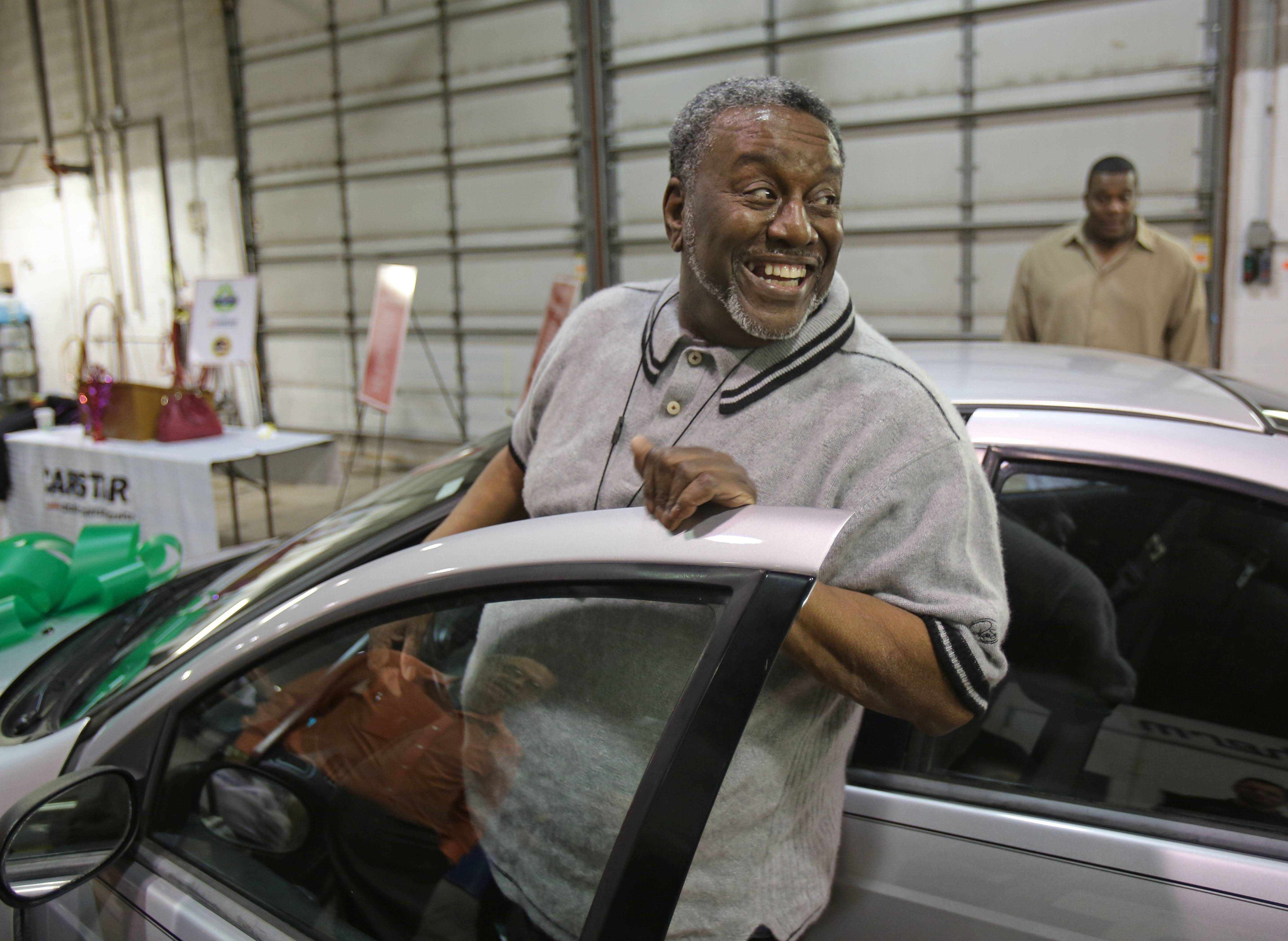 Milton Whitington, 63, of Waukegan is all smiles Wednesday as he gets into his car. The refurbished Dodge Neon was presented to Whittington through a program called Recycled Ride sponsored by Carstar in Mundelein and Esurance.