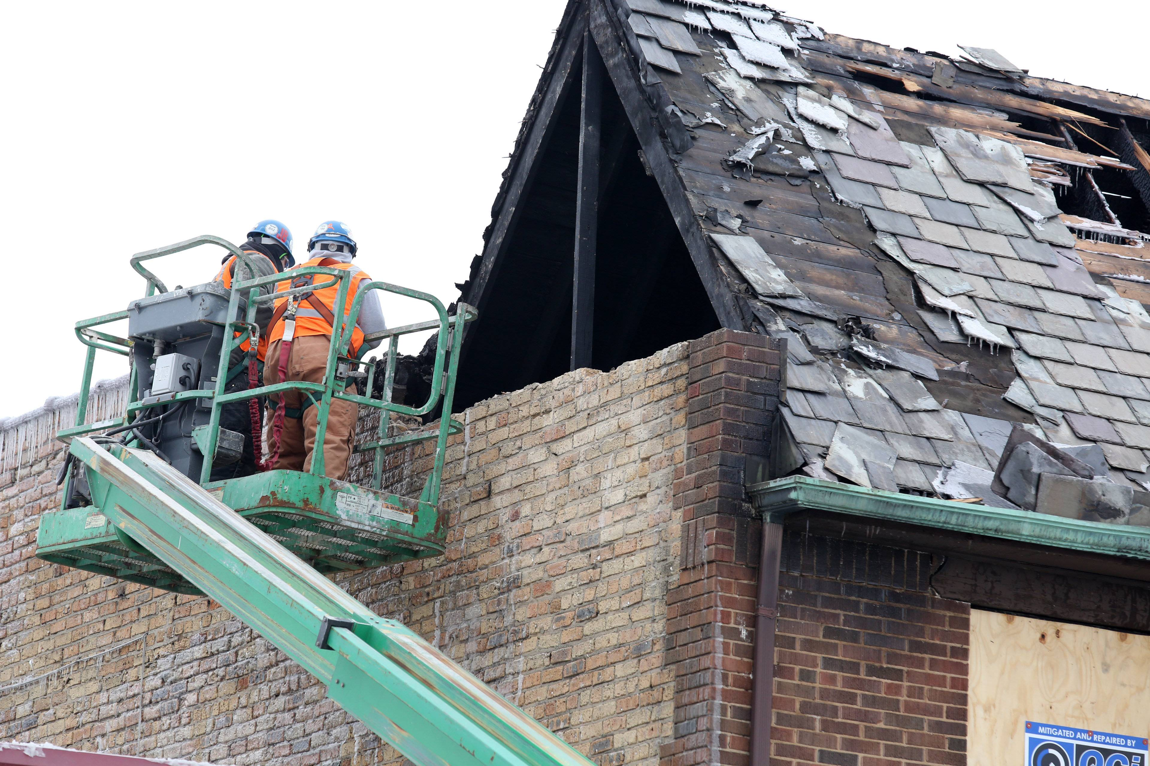 Workers begin Wednesday to demolish a portion of the building damaged by an early Sunday morning fire.