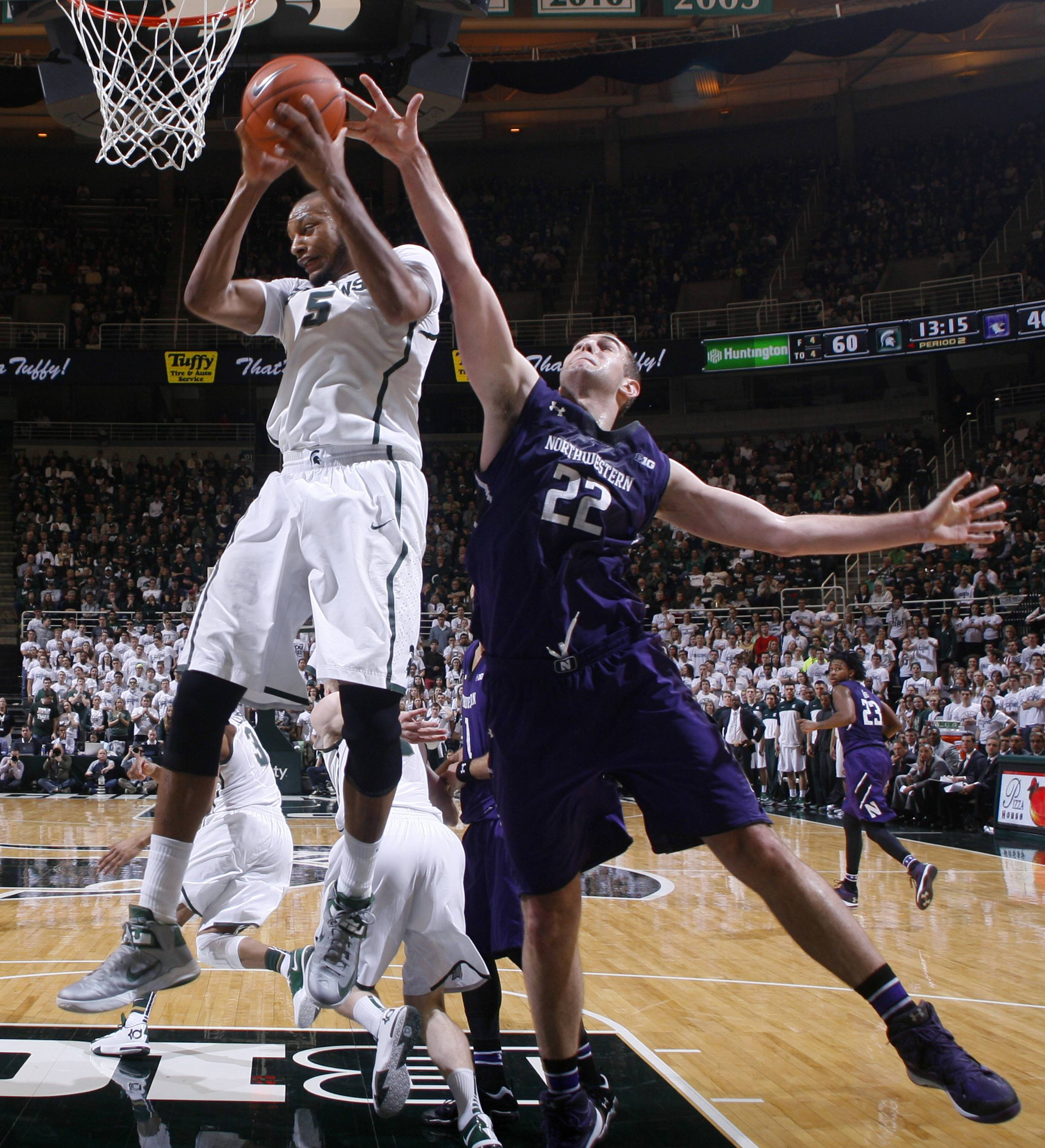 Michigan State's Adreian Payne (5) pulls down a rebound against Northwestern's Alex Olah (22) during the second half of an NCAA college basketball game, Thursday, Feb. 13, 2014, in East Lansing, Mich. Payne led Michigan State with 20 points and 14 rebounds in an 85-70 win.
