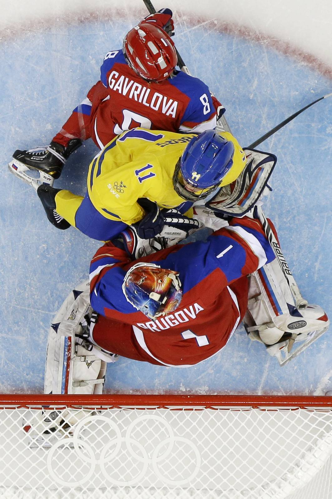 Cecilia Ostberg of Sweden is sandwiched between Iya Govrilova (8) and goalkeeper Anna Prugova of Russia (1) as she attacks the goal.