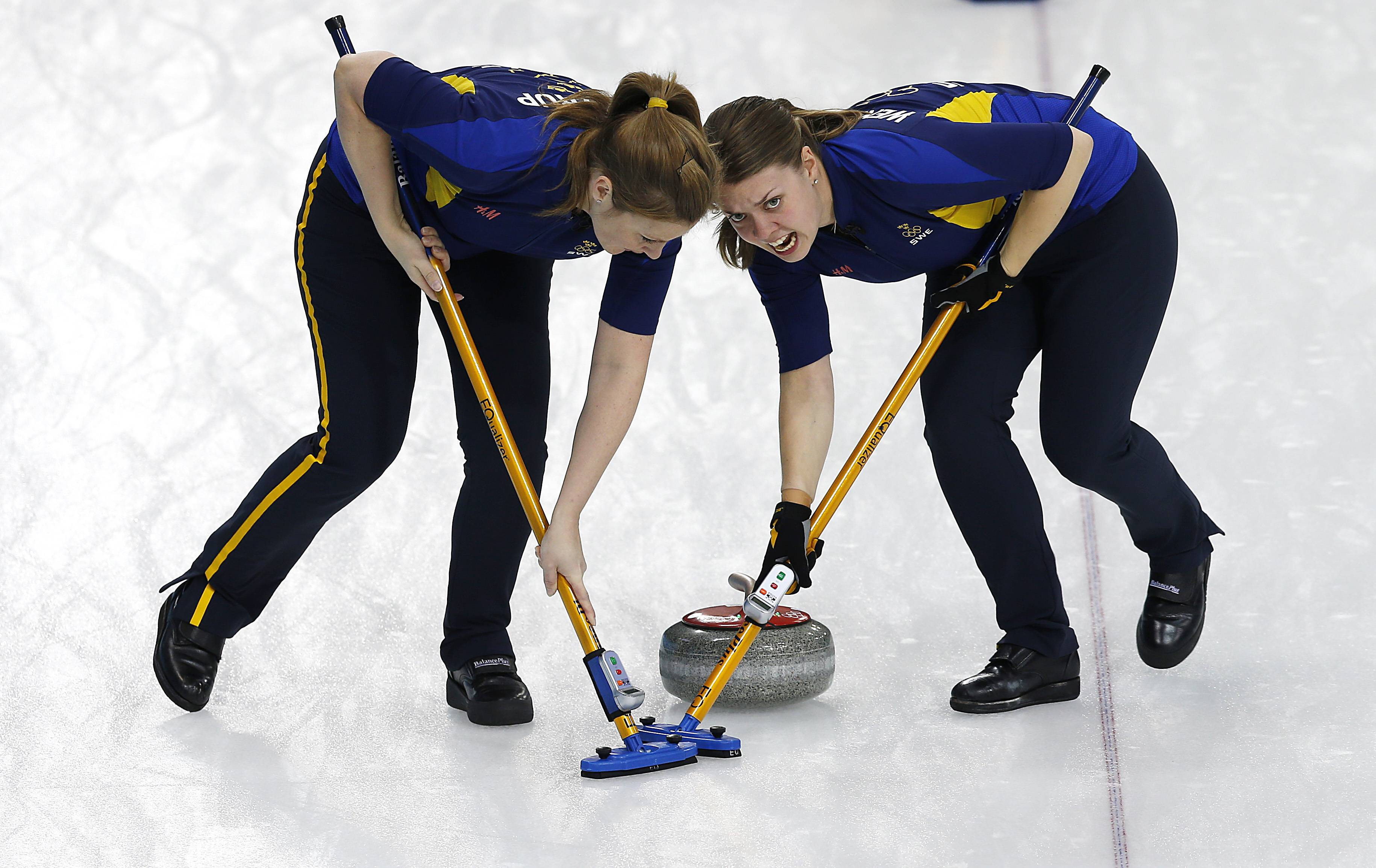 Sweden's Maria Wennerstroem, right and Christina Bertrup, left, sweep the ice during the women's curling competition against Denmark.