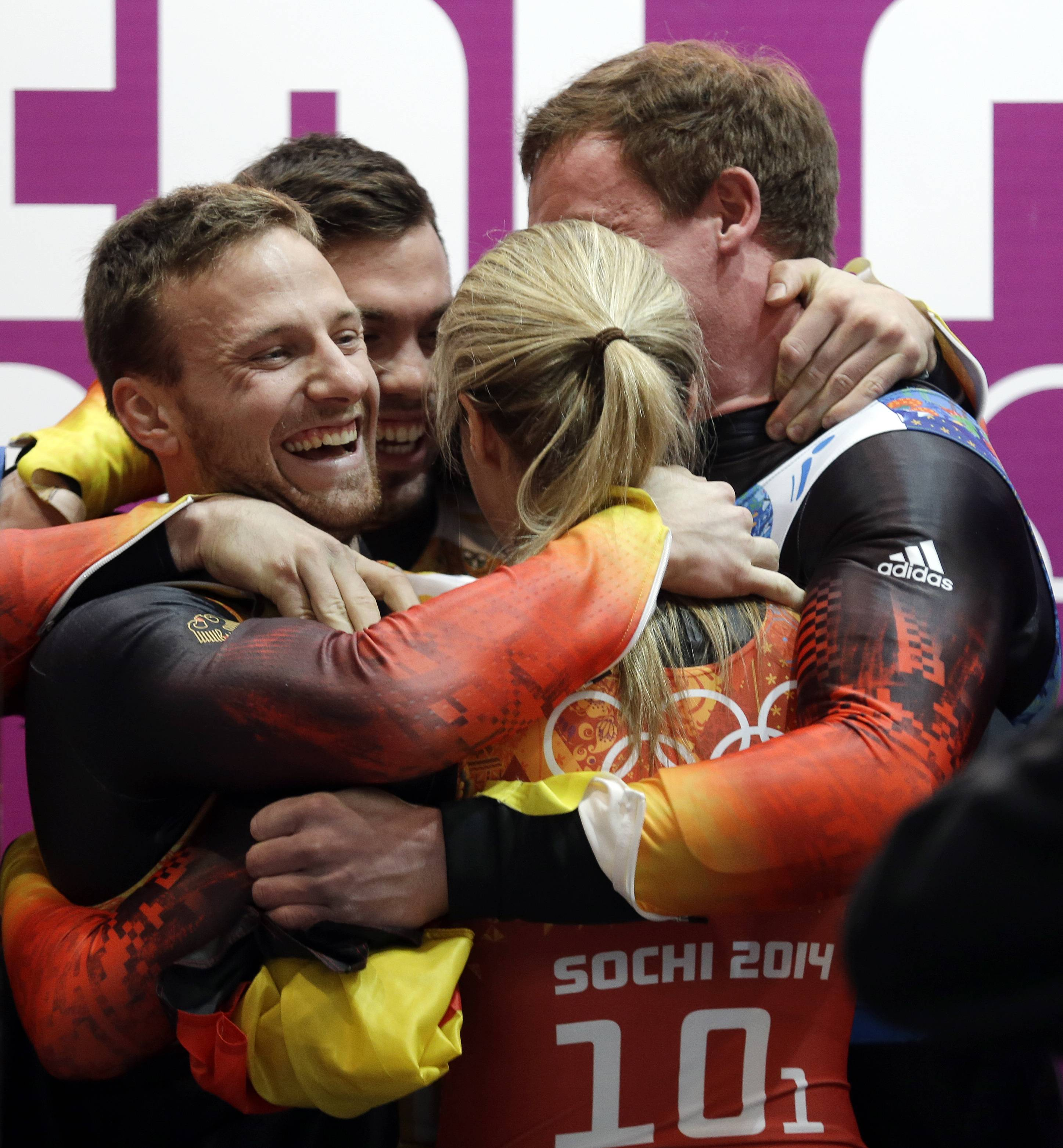 The German team celebrate after they won the gold medal during the luge team relay competition.