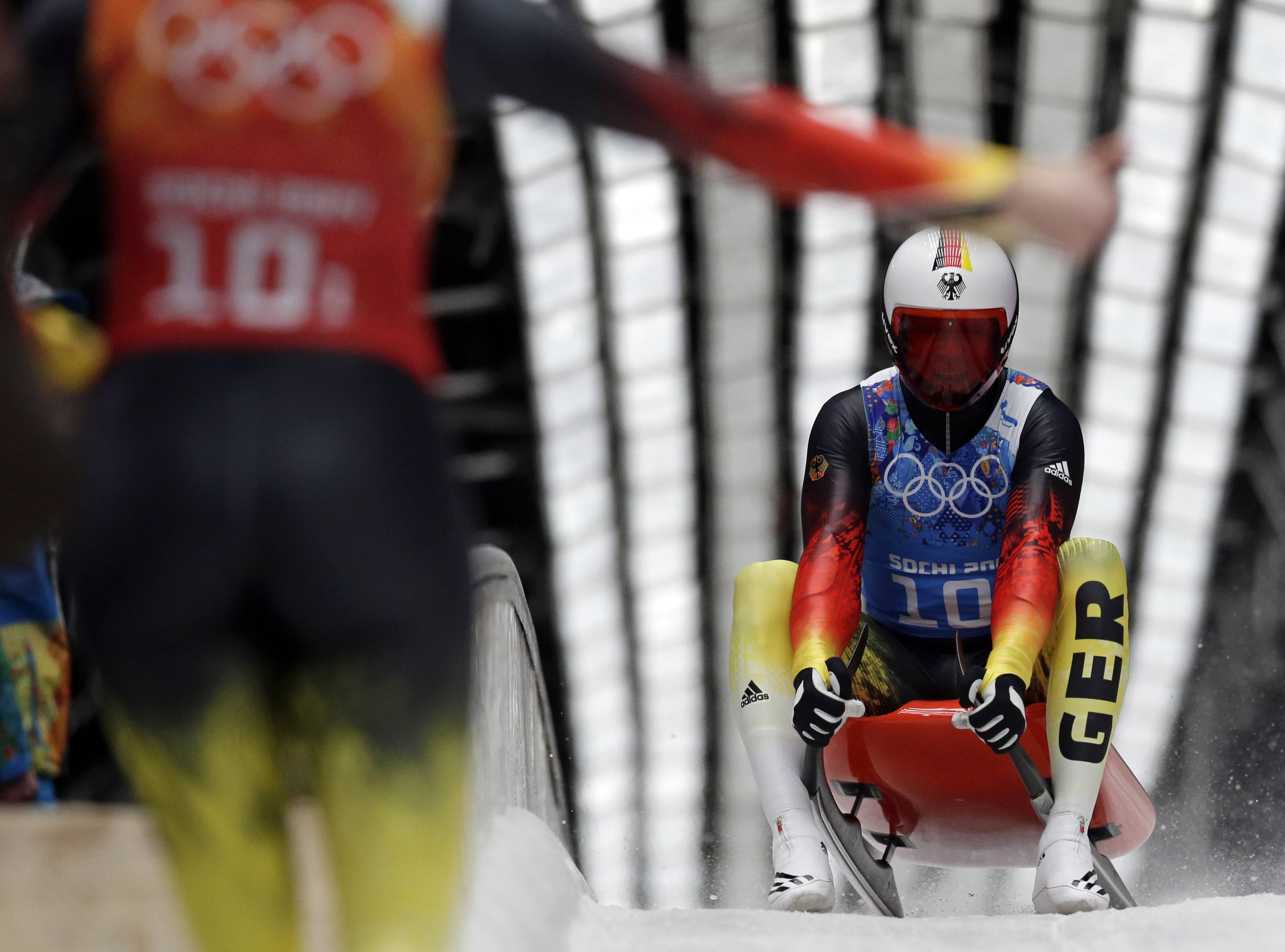 Germany's Felix Loch is greeted in the finisg area by teammate Natalie Geisenberger during the luge team relay competition.