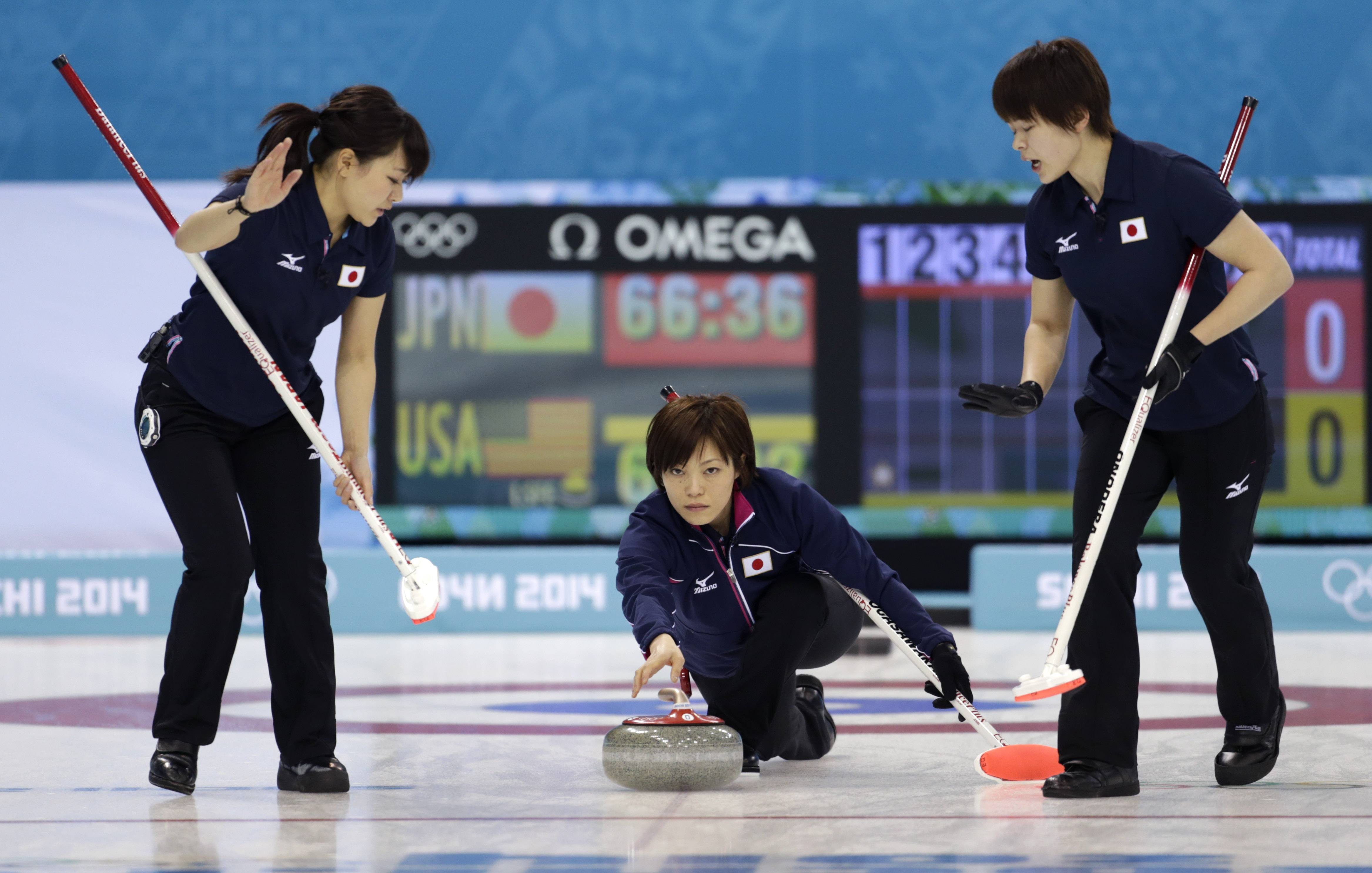 Japan's skip skip Ayumi Ogasawara, center, delivers the rock to sweepers Chinami Yoshida, left, and Kaho Onodera during women's curling competition against the United States.