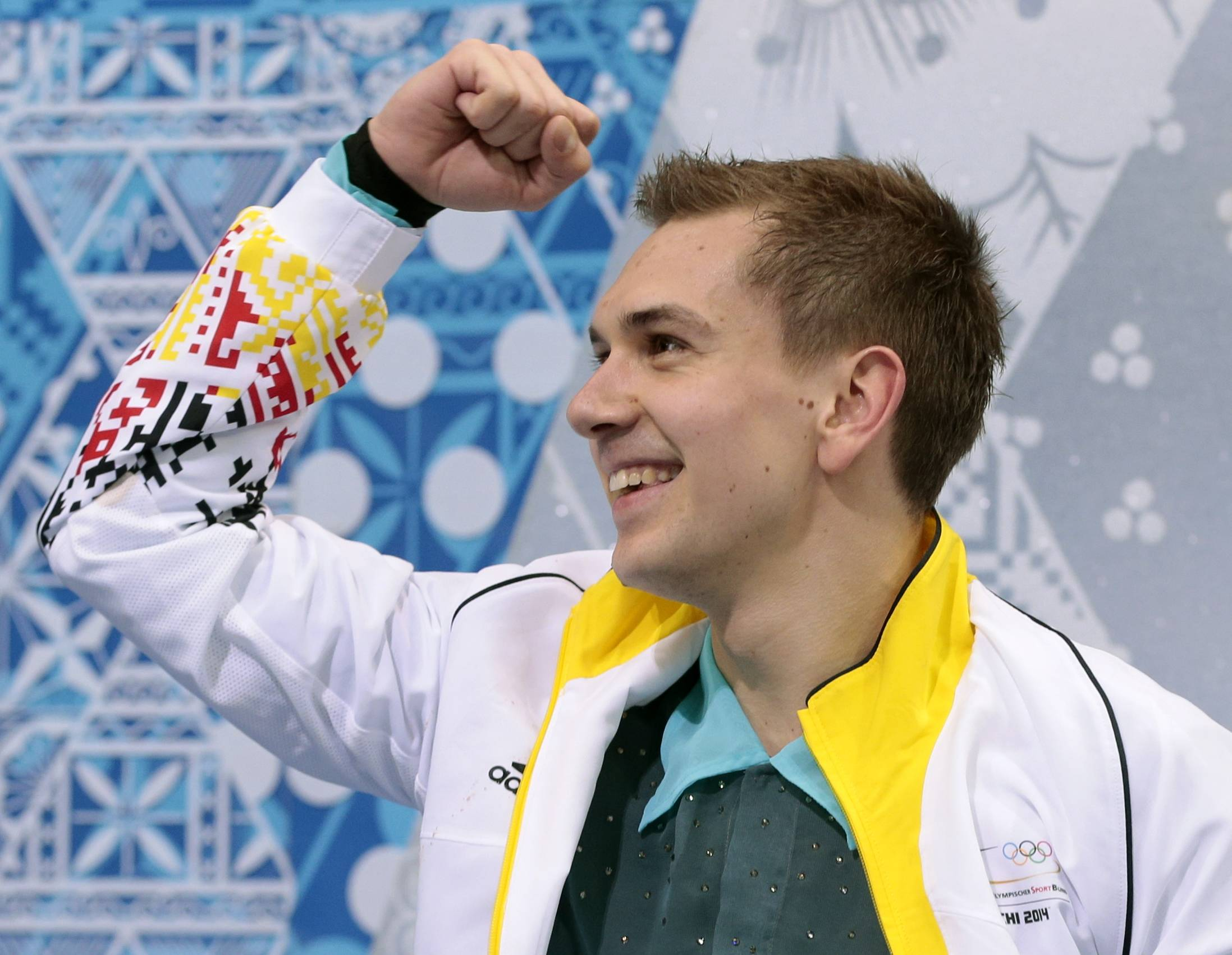 Peter Liebers of Germany gestures as he waits in the results area after the men's short program figure skating competition.