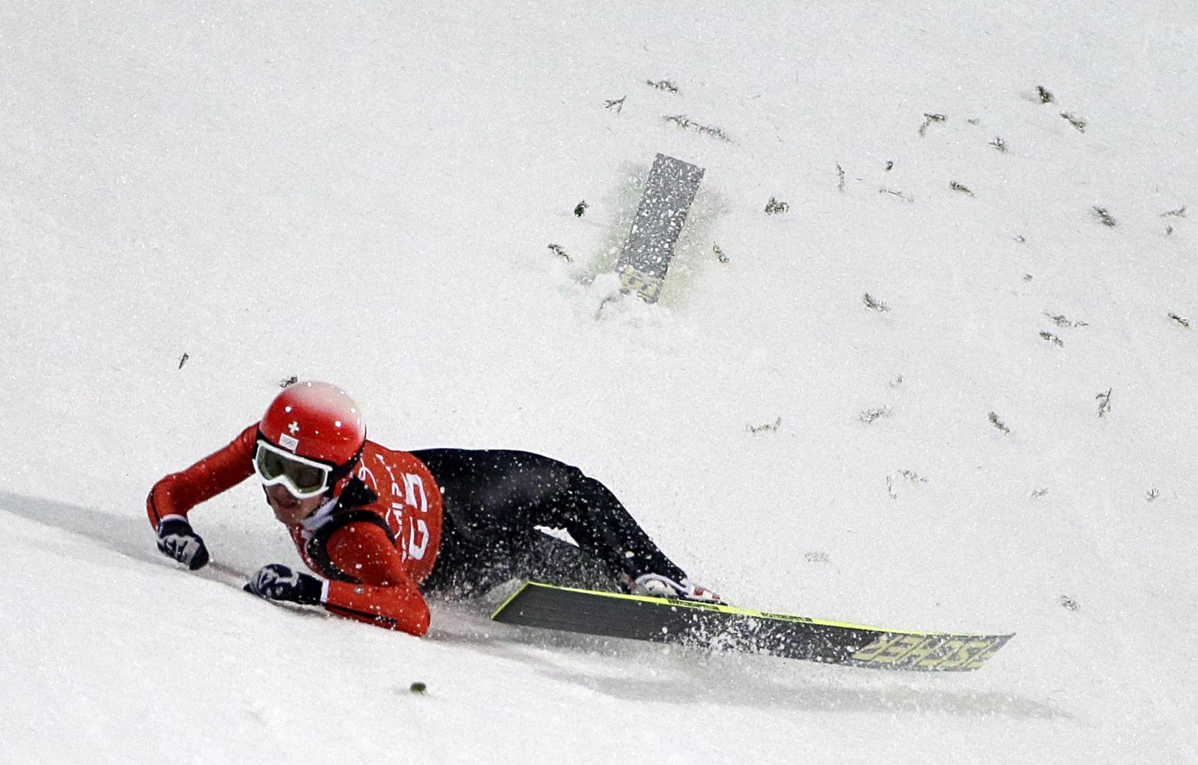 Switzerland's Simon Ammann crashes during a training session for the men's large hill ski jumping .