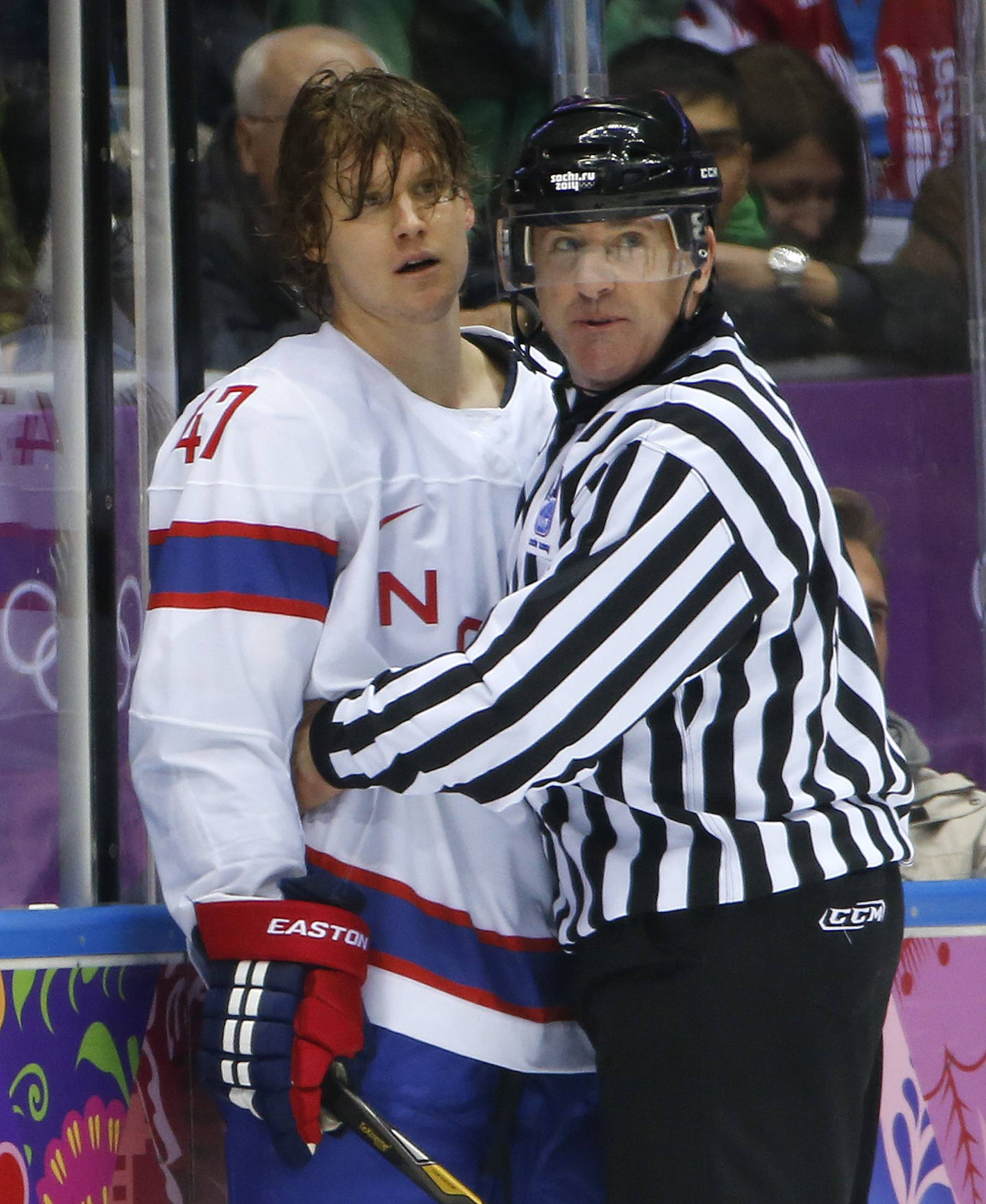 A referee holds back Norway defenseman Alexander Bonsaksen after a scuffle with Canada forward Chris Kunitz.