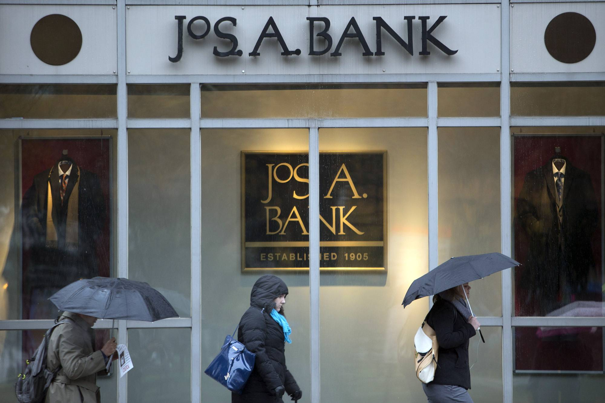 Pedestrians carrying umbrellas walk past a Jos. A. Bank Clothiers Inc. store in Washington, D.C., U.S., on Tuesday, Nov. 26, 2013. Men's Wearhouse Inc., which less than two weeks ago let a takeover bid from Jos. A. Bank Clothiers expire without entering discussions, today offered to buy its smaller rival for about $1.54 billion. Photographer: Andrew Harrer/Bloomberg