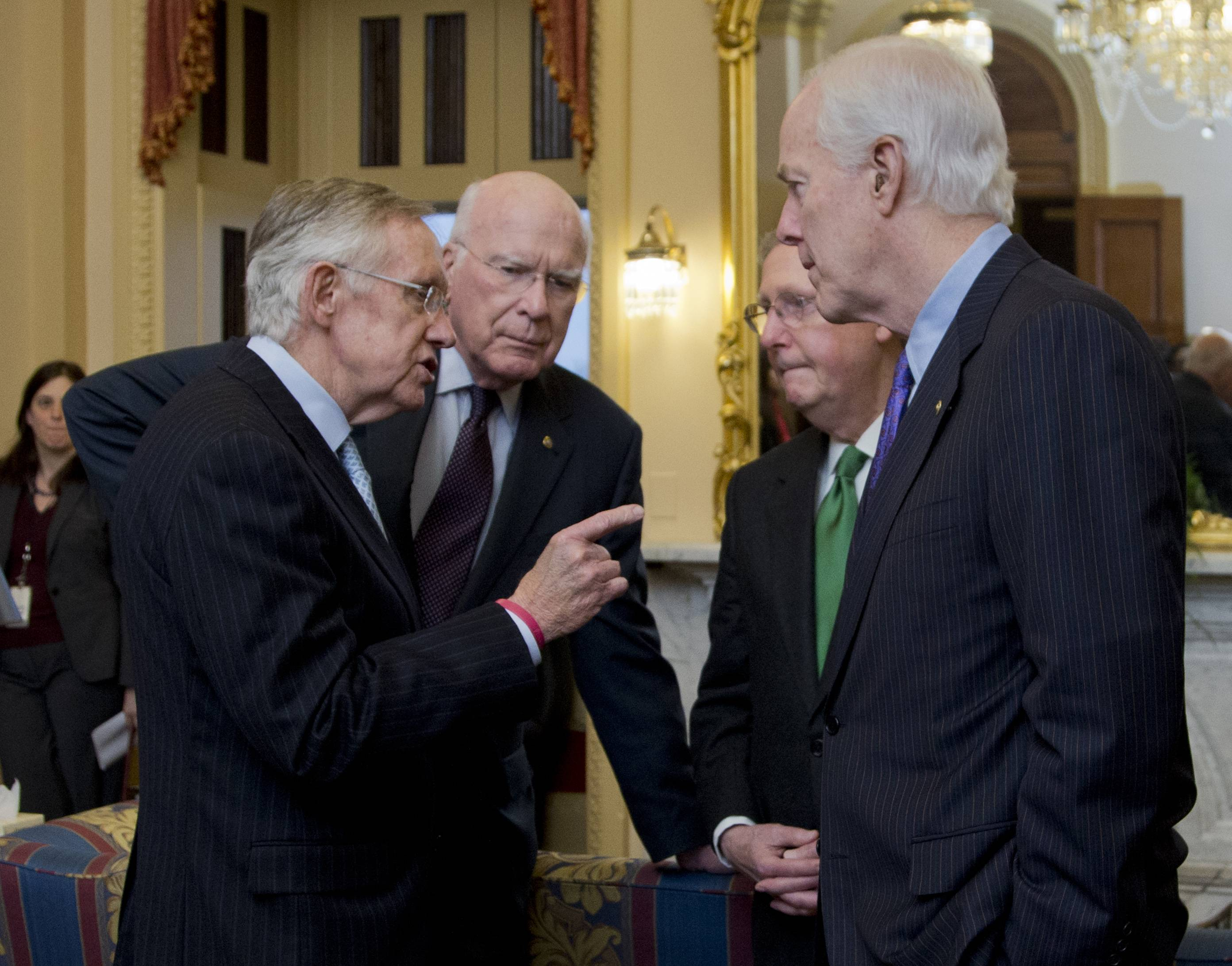 Senate Majority Leader Harry Reid, D-Nev., from left, Sen. Patrick Leahy, D-Vt., Republican Leader Mitch McConnell, R-Ky., and Sen. John Cornyn, R-Texas, talk as they wait in the majority leader's office. The lawmakers voted on must-pass legislation to increase the government's debt limit and after their leaders decided to drop the parliamentary equivalent of a curtain on the voting until its outcome was assured