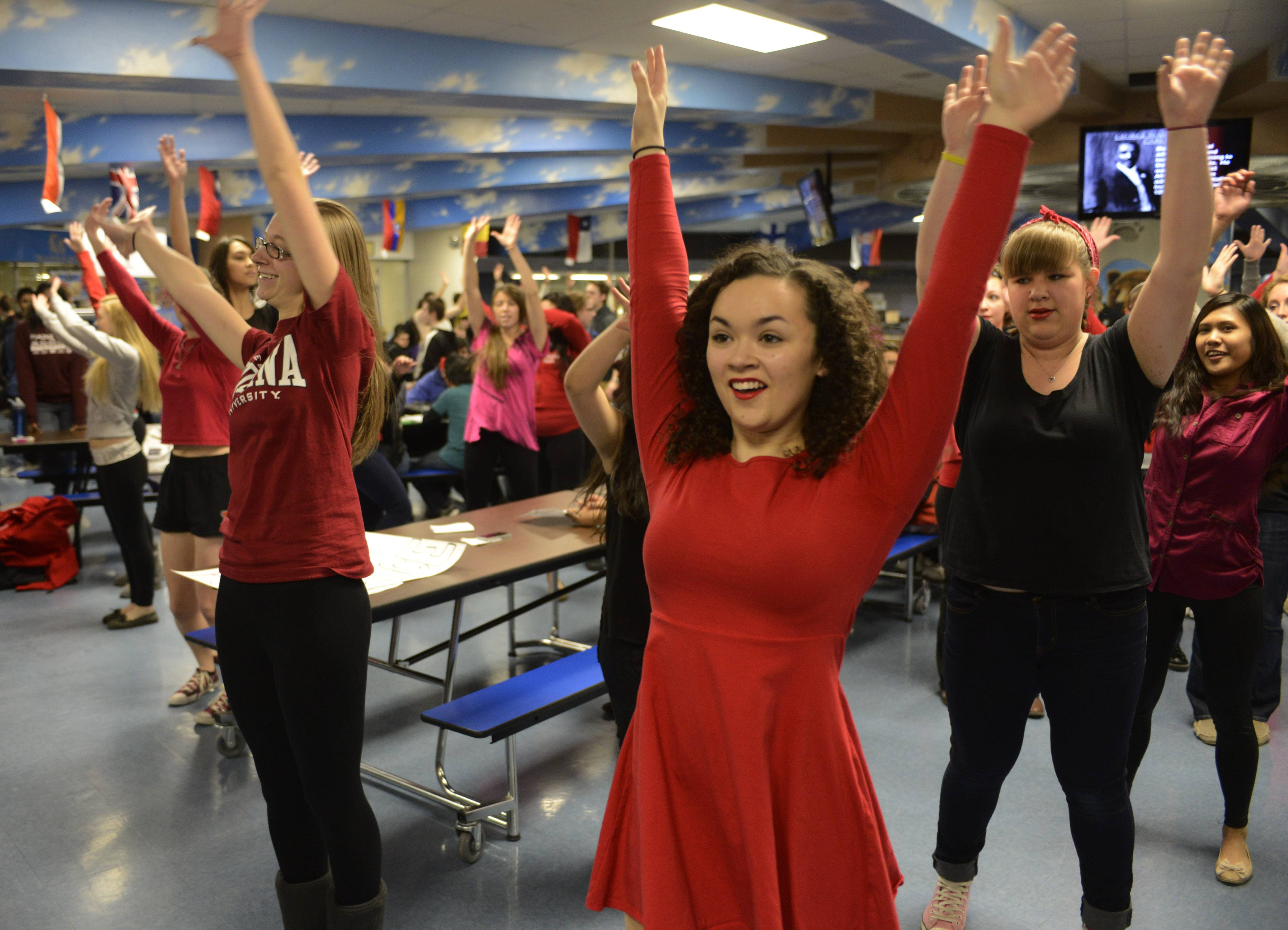 "Students including Lizzie Karras, right, dance during a ""One Billion Rising"" flash mob event in the Maine West High School cafeteria Friday morning in Des Plaines to raise awareness about violence against women."