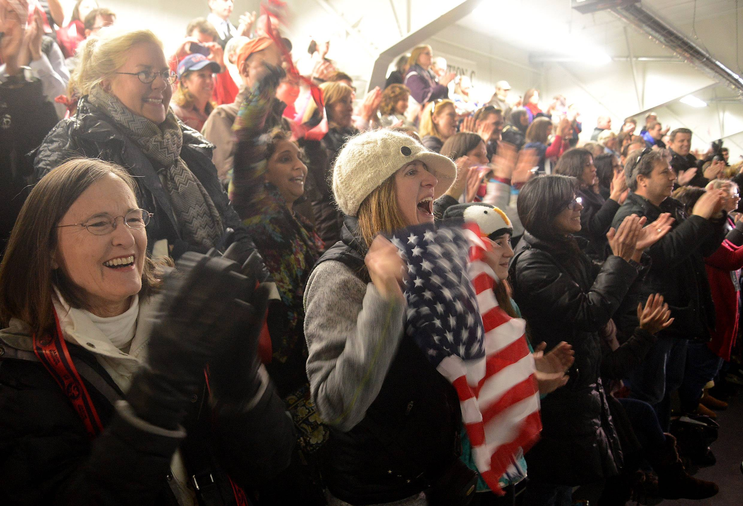 Debra Knight, of Lake Villa, holds a flag and cheers during a Friday viewing party at the Centennial Ice Arena in Highland Park for hometown Olympic skater Jason Brown.