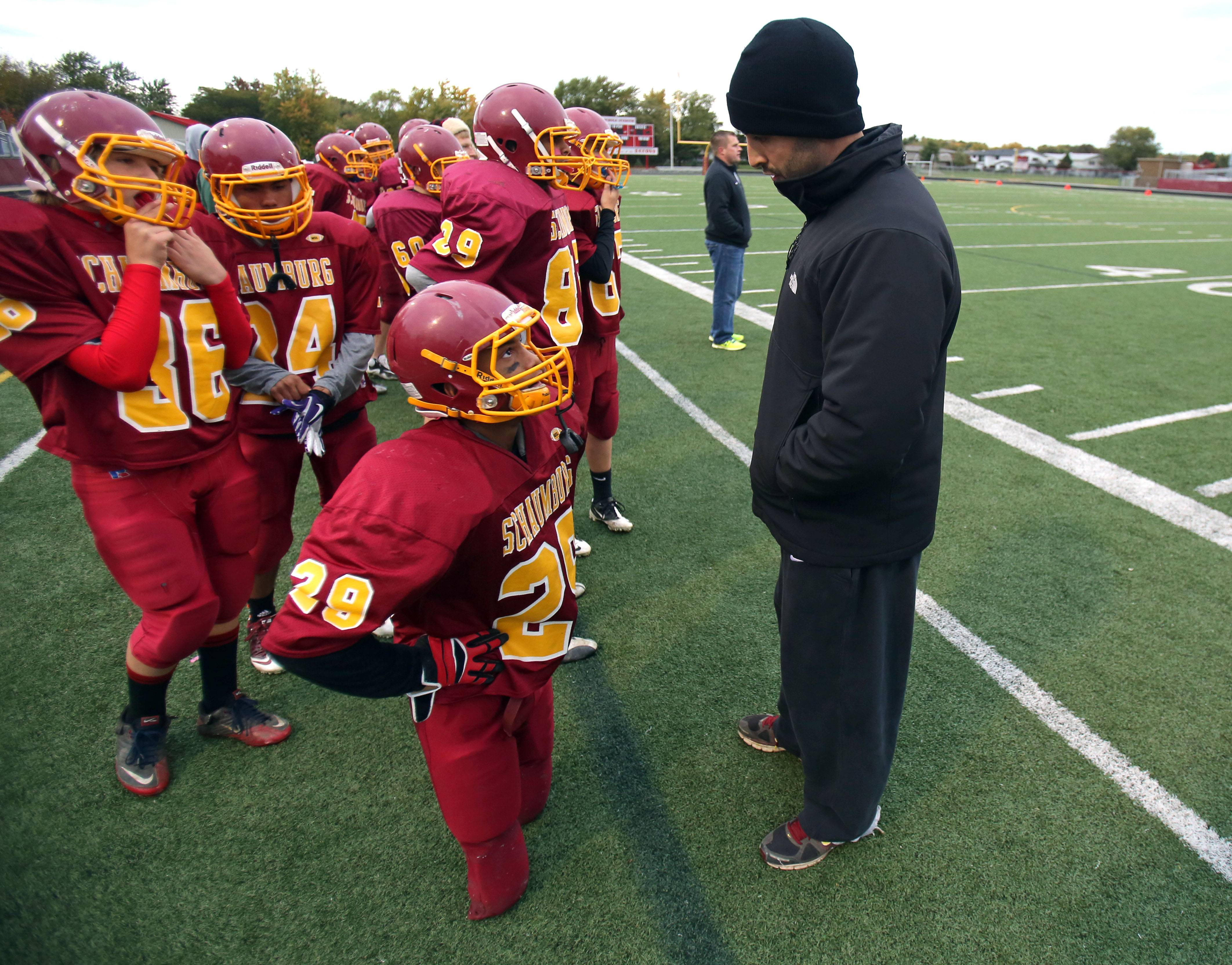 Schaumburg High School freshman Sabik Corhan listens to one of his coaches prior to going into the game. Born without shin or ankle bones, Corhan has learned to keep up with his teammates without the use of his prosthetic legs.