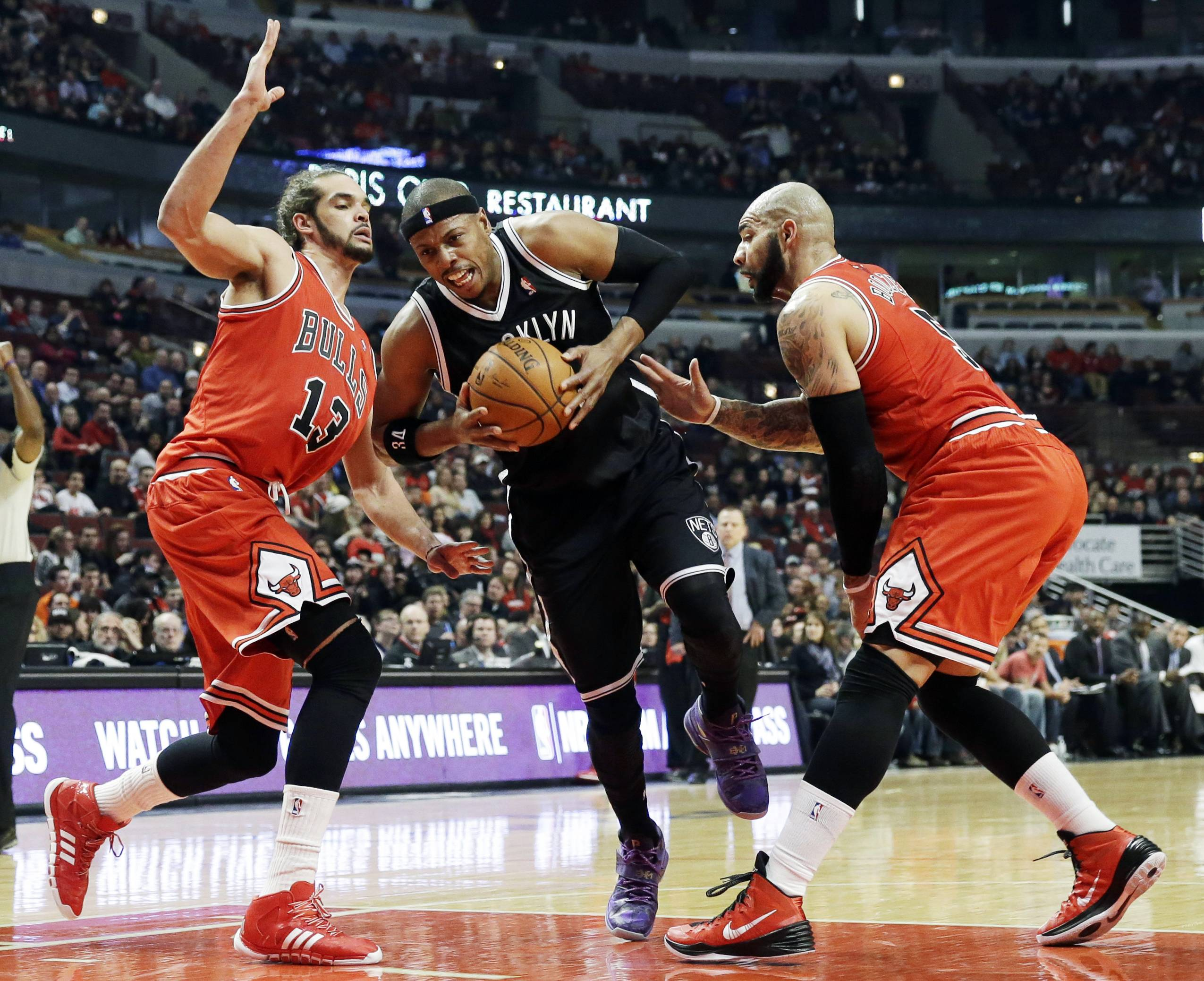 Brooklyn Nets forward Paul Pierce, center, drives to the basket as Chicago Bulls center Joakim Noah, left, and forward Carlos Boozer guard during the first half of an NBA basketball game in Chicago on Thursday, Feb. 13, 2014. (AP Photo/Nam Y. Huh)