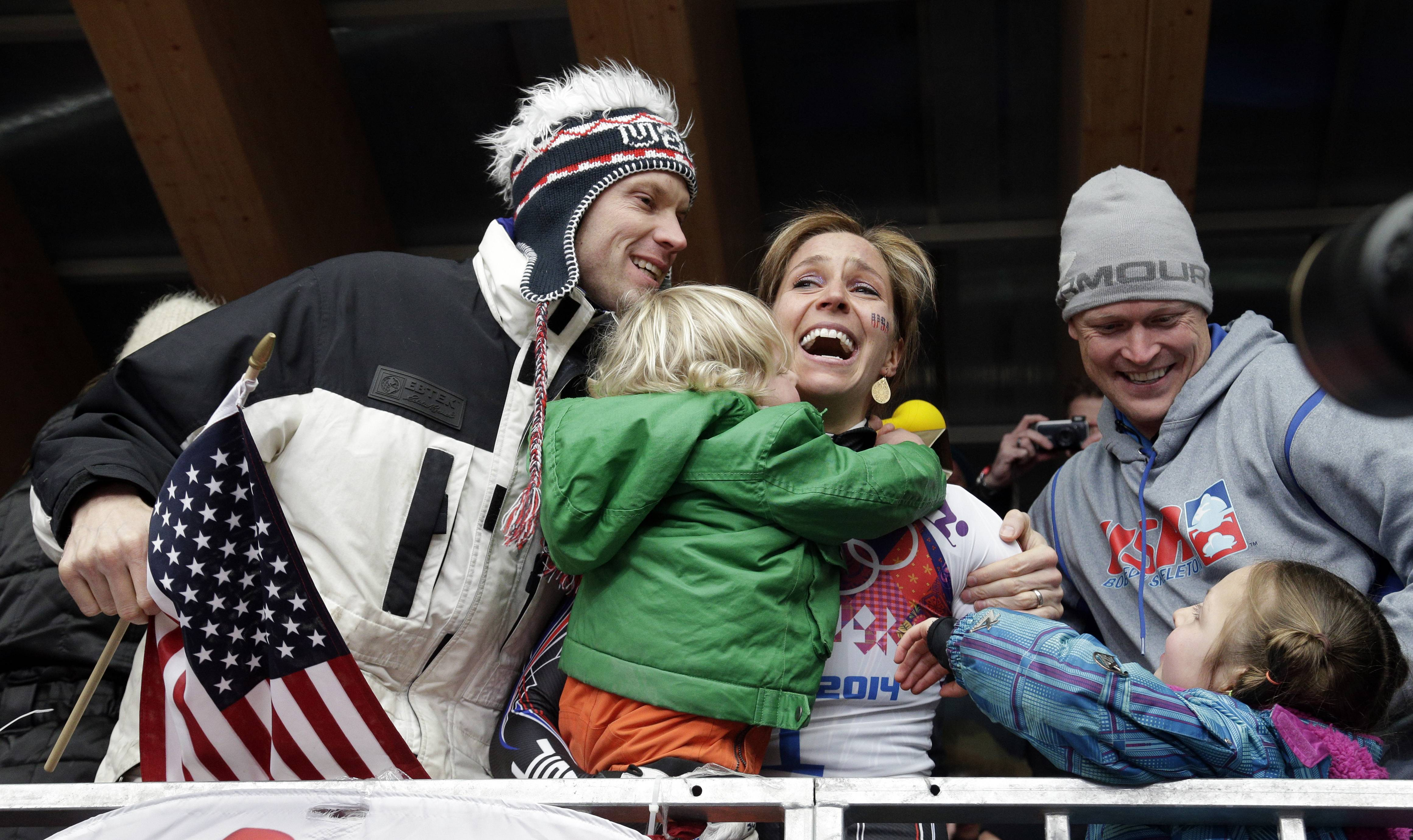 Noelle Pikus-Pace of the United States celebrates with her husband, Janson Pace, right, and her children, Traycen, left, and Lacee, lower right, after she won the silver medal during the women's skeleton competition.