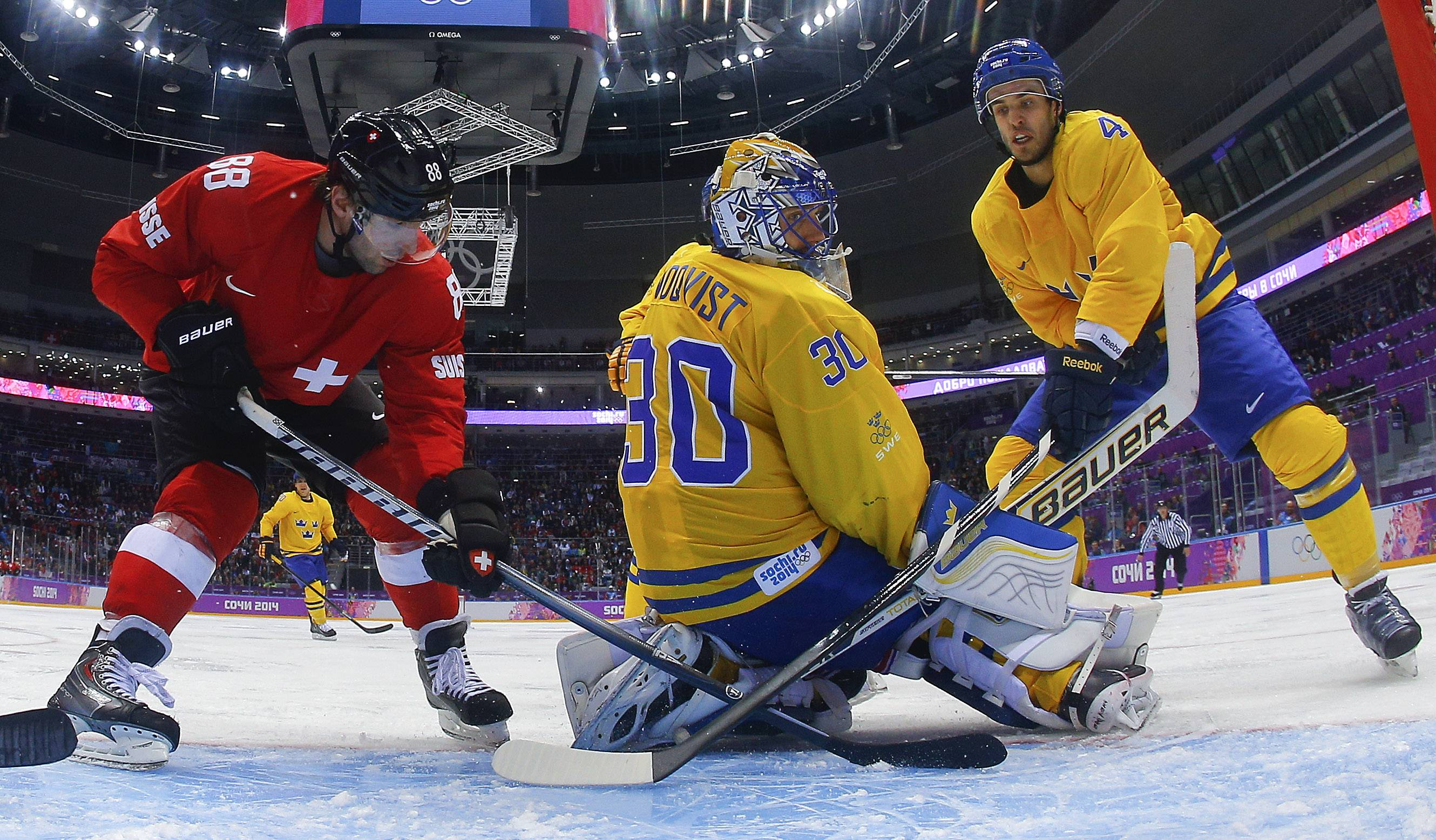 Switzerland forward Kevin Romy (88) and Sweden defenseman Niklas Hjalmarsson look for the rebound behind goaltender Henrik Lundqvist in the third period of a men's ice hockey game at the 2014 Winter Olympics, Friday, Feb. 14, 2014 in Sochi, Russia. Sweden won 1-0.