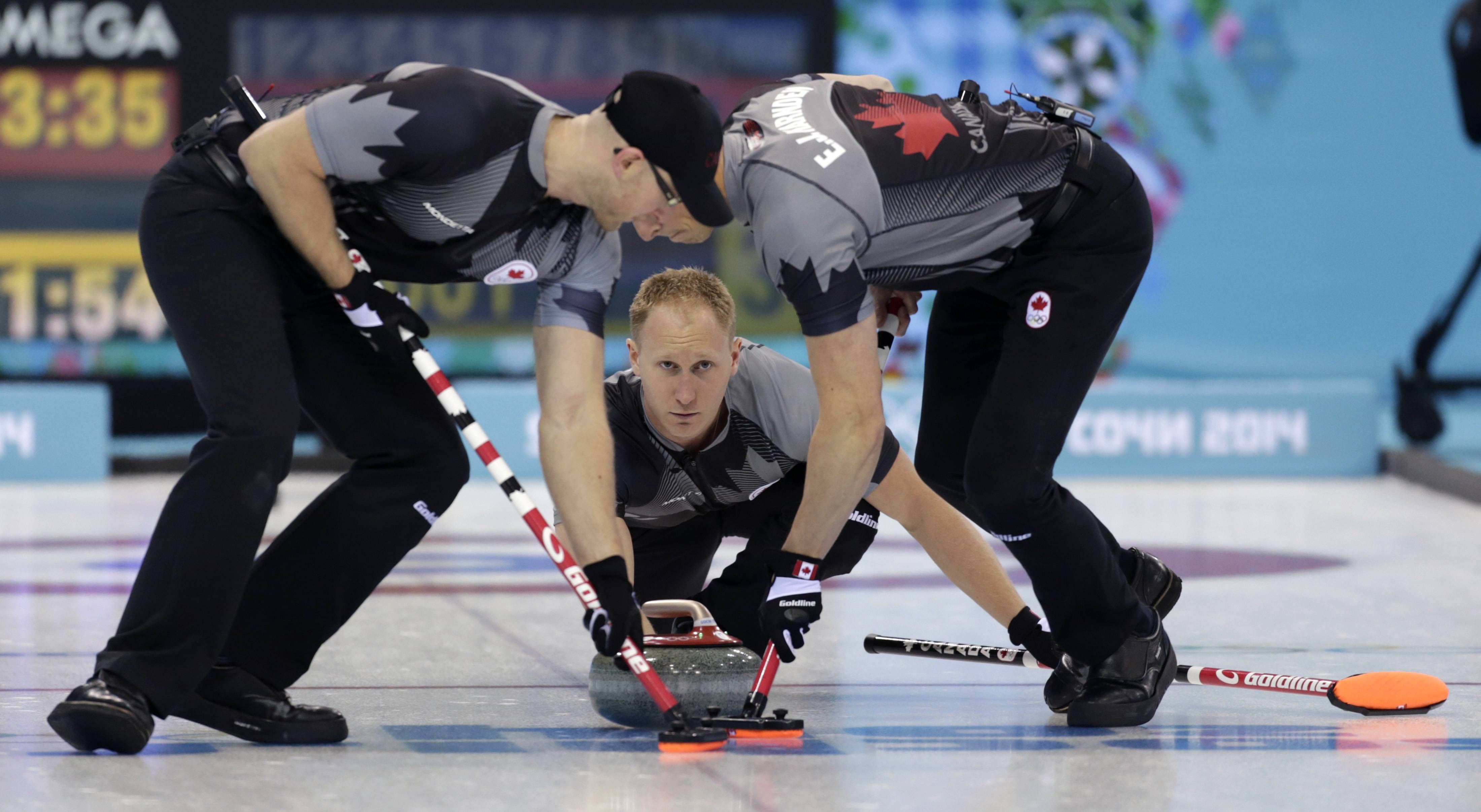 Canada's skip Brad Jacobs, center, delivers the rock to his sweepers Ryan Harnden, left, and E.J. Harnden Friday during men's curling competition against Norway at the 2014 Winter Olympics in Sochi, Russia.