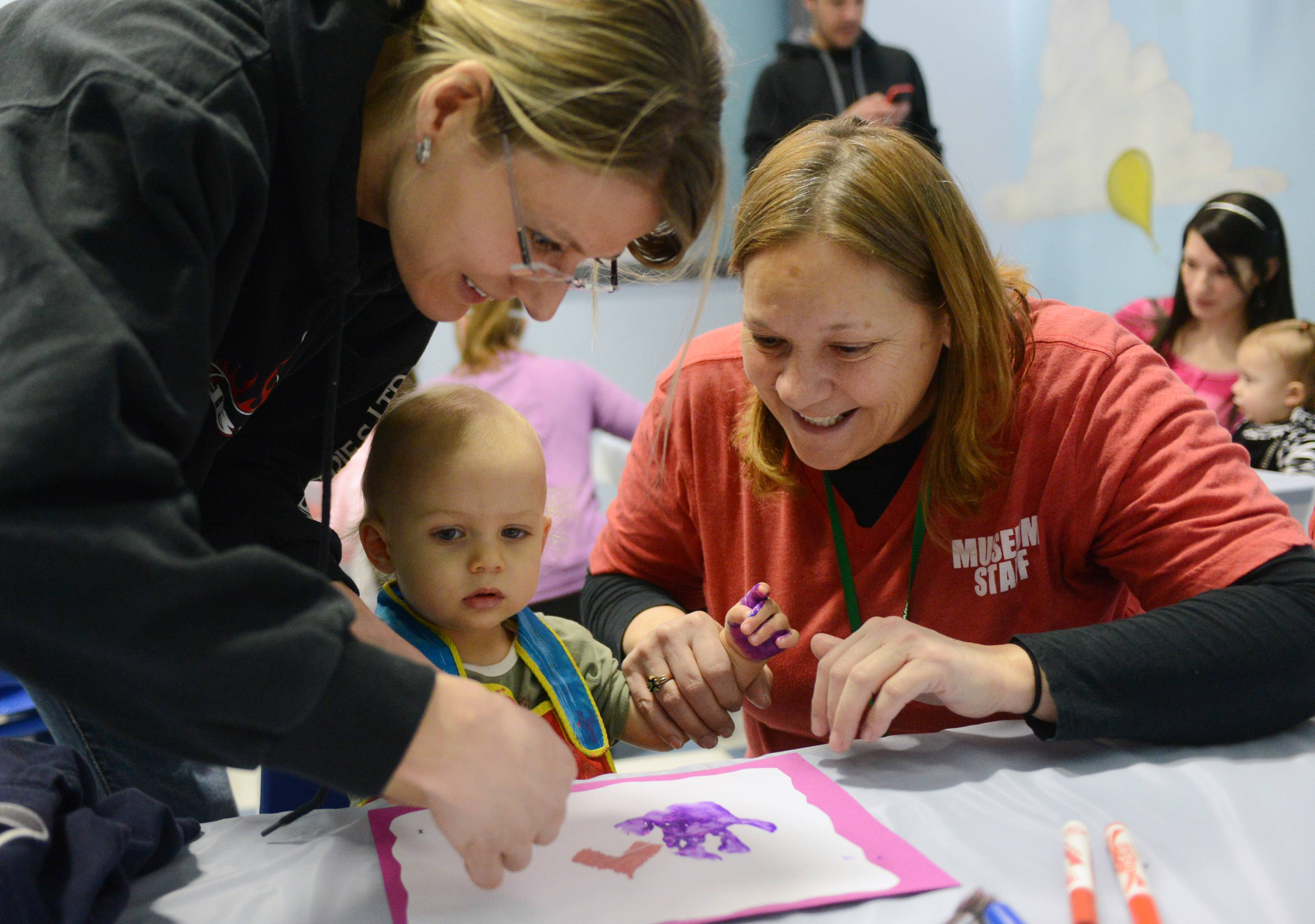 Children's Neighborhood Museum staff member Jeanine Gutantes, right, helps Sacha Street and her 13-month-old son, Sage, both of Grayslake, make a Valentine's Day art piece Friday during the Cupids' Cupcakes program in Round Lake.