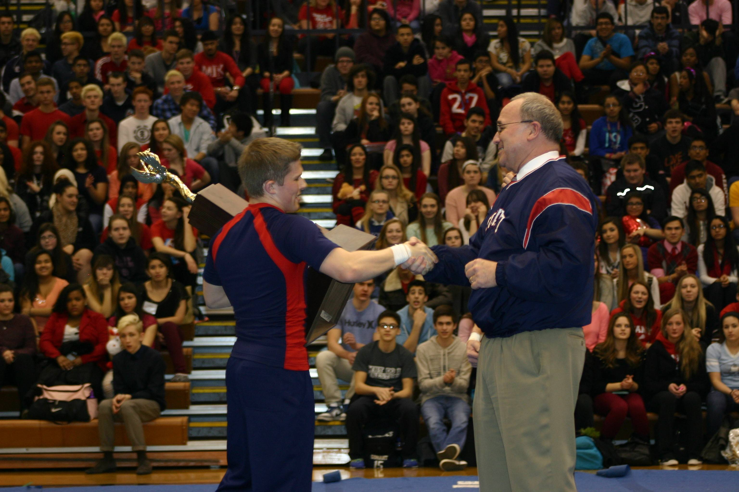 Conant senior cheerleader Scott Ruzanski presents Principal Tim Cannon with the state championship trophy at Friday's pep rally at the Hoffman Estates school. The coed squad performed its title-winning routine during the pep rally.