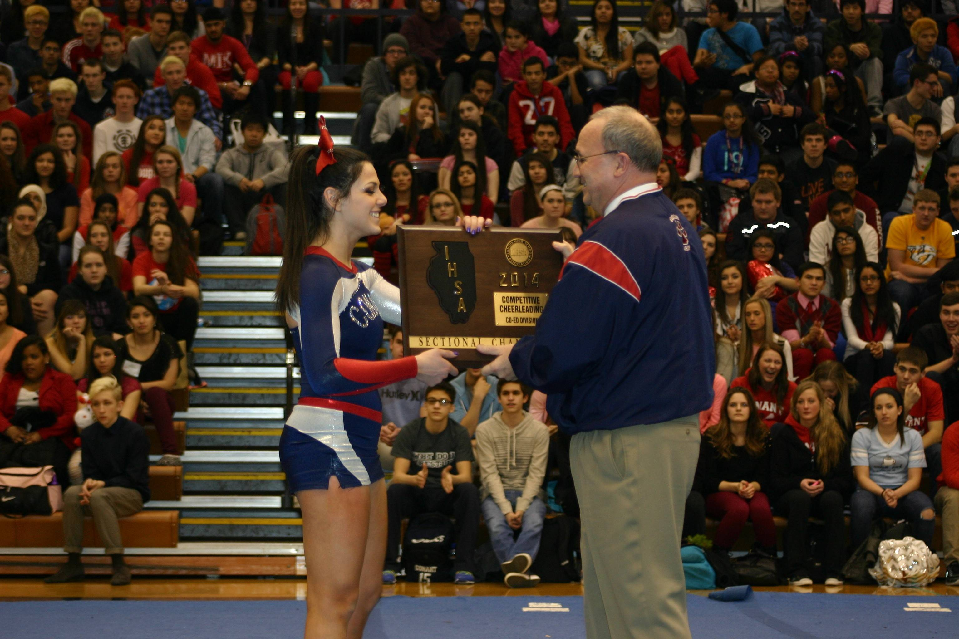 Senior cheerleader Hannah Shoro presents Conant Principal Tim Cannon with the sectional title plaque at a school pep rally Friday.