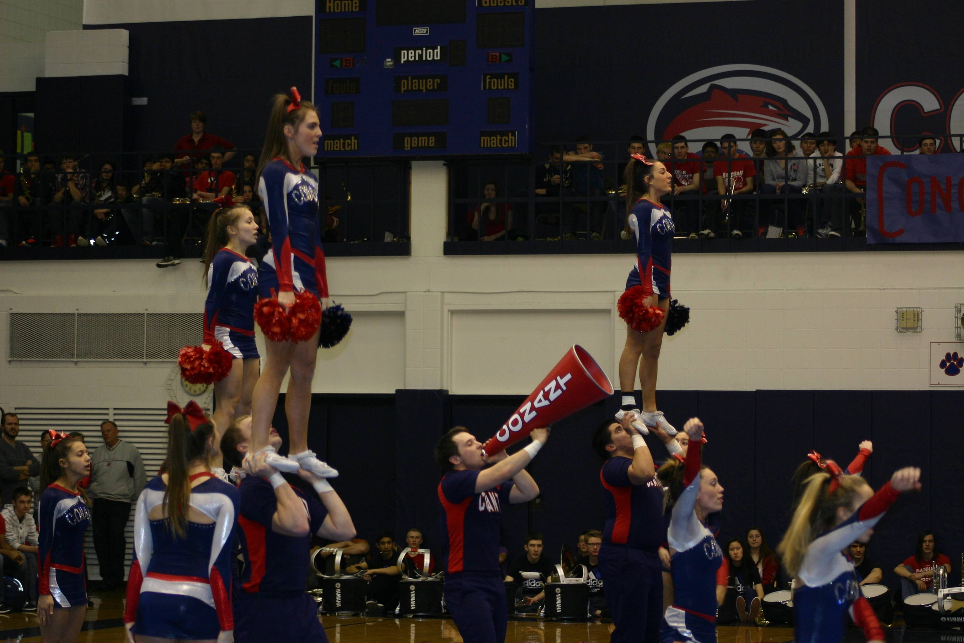 The Conant High School coed cheerleading squad performs its state championship-winning routine at a pep rally Friday.