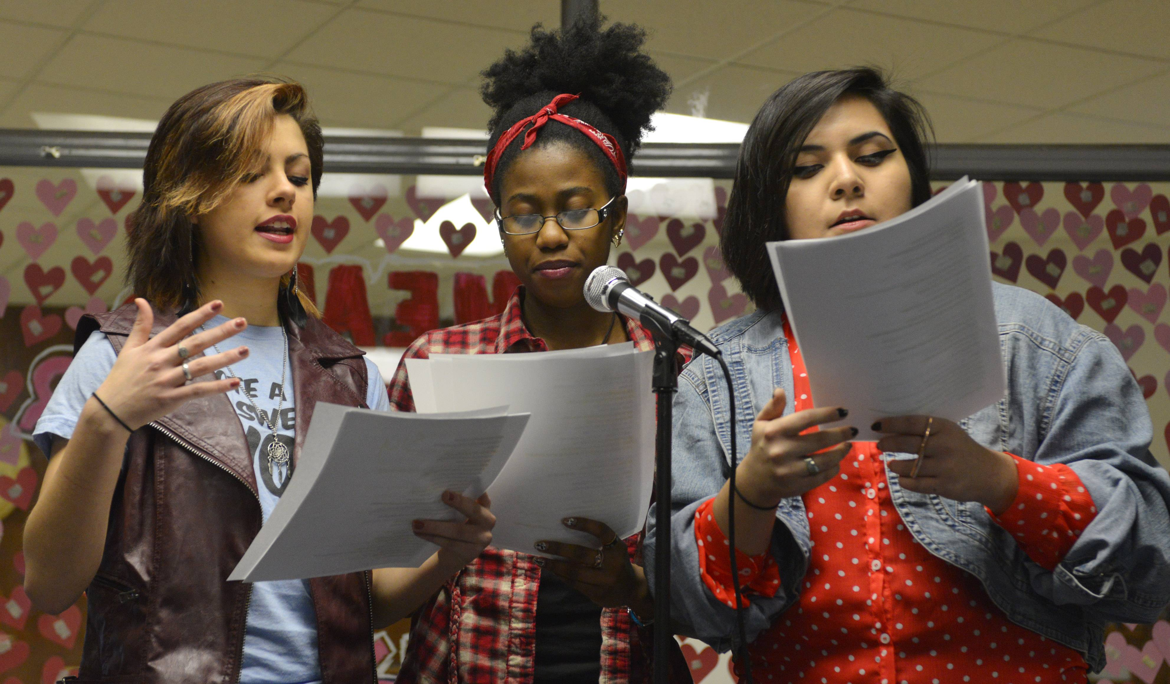 "Left to right, seniors Sylvia Mendez, Malaika Spencer and Samantha Arriozola read poetry during a ""One Billion Rising"" flash mob event in the Maine West High School cafeteria Friday morning in Des Plaines to raise awareness about violence against women."