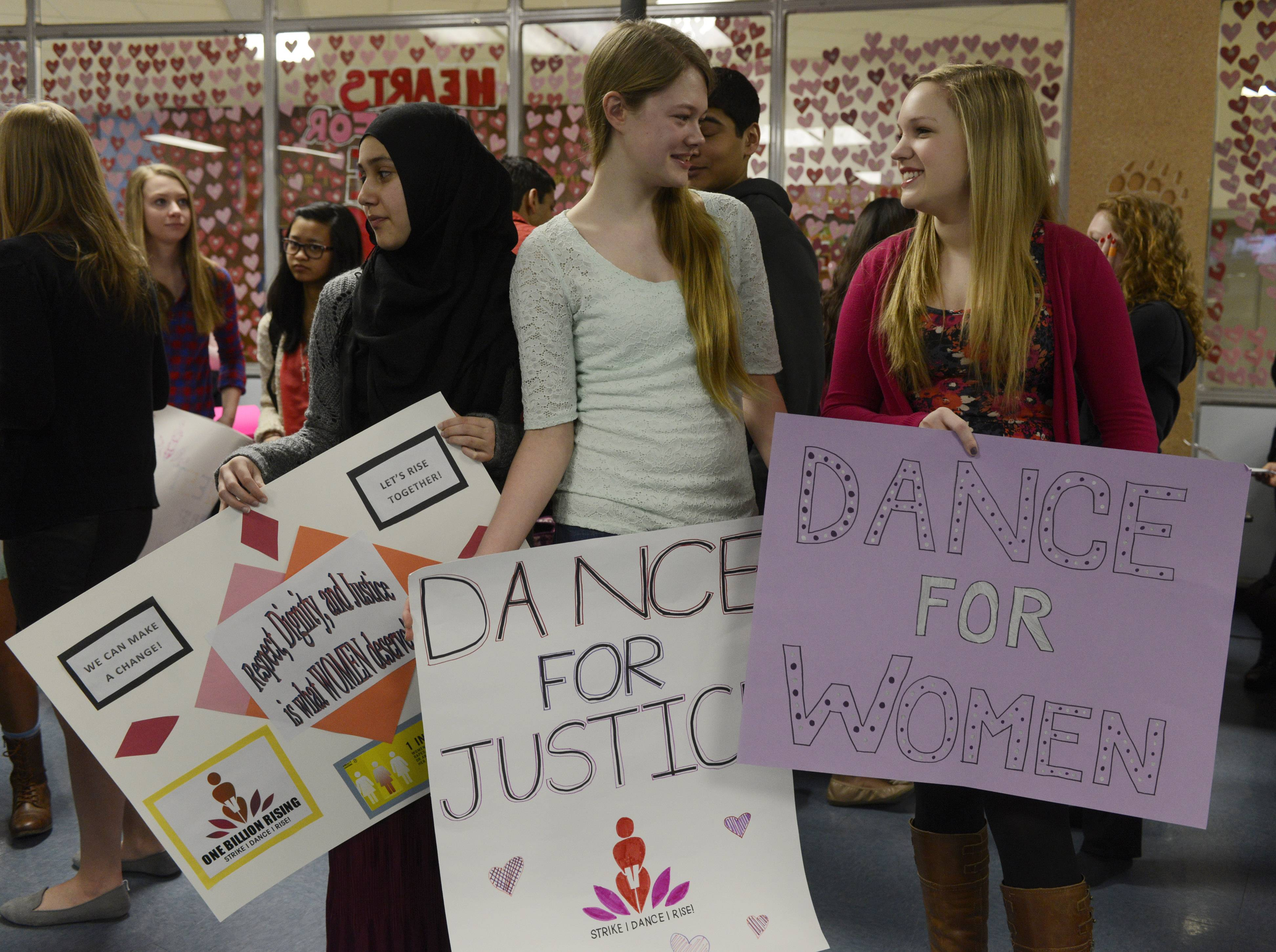 "Left to right, sophomores Medina Furqan, Melissa Holzer and Haley Wedge hold posters during a ""One Billion Rising"" flash mob event in the Maine West High School cafeteria Friday morning in Des Plaines to raise awareness about violence against women."
