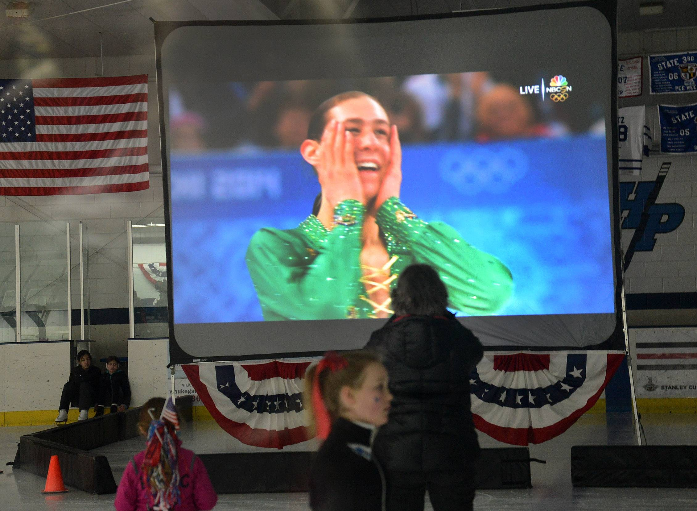 Olympic figure skater Jason Brown of Highland Park's final skate broadcast on the big screen at the Centennial Ice Arena during a viewing party Friday.