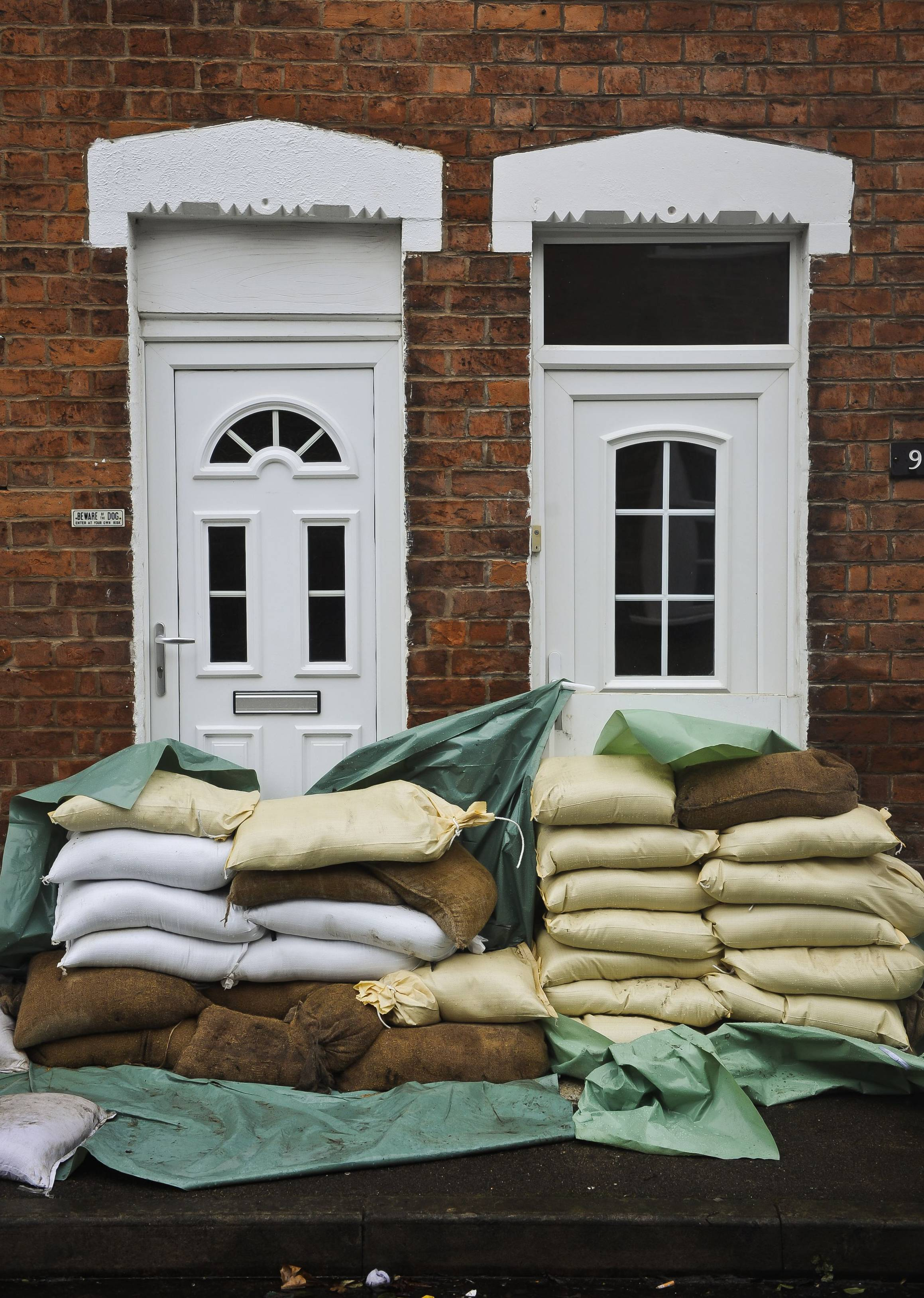 Sandbags form a levee protecting the front doors of homes in Gloucester, southwest England, as the region reacts to an increased flood threat alert Friday.