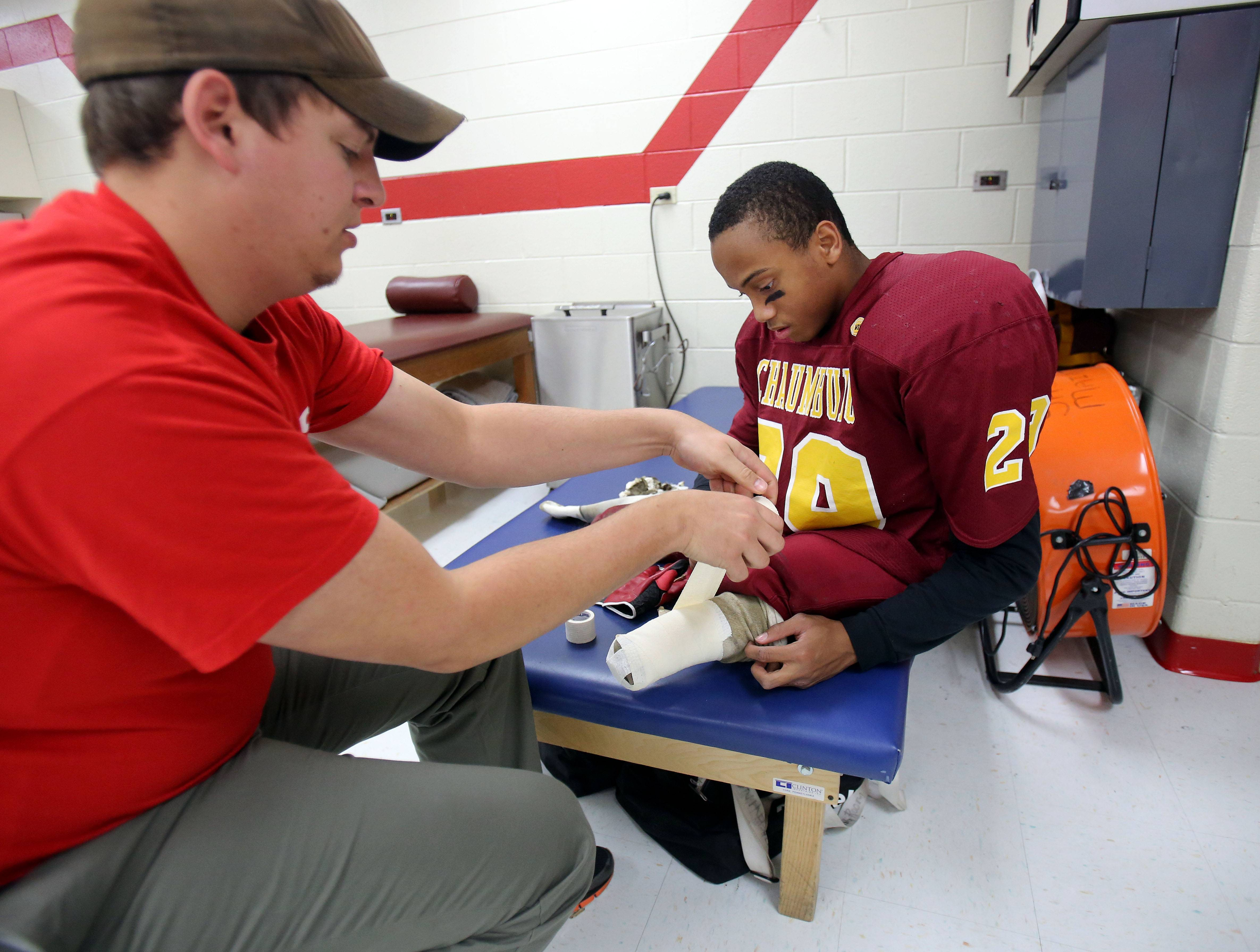Schaumburg athletic trainer Josh Goray, left, tapes up Sabik Corhan's legs prior to their final game of the season. Corhan is not allowed to play with his prosthetic legs for safety reasons.