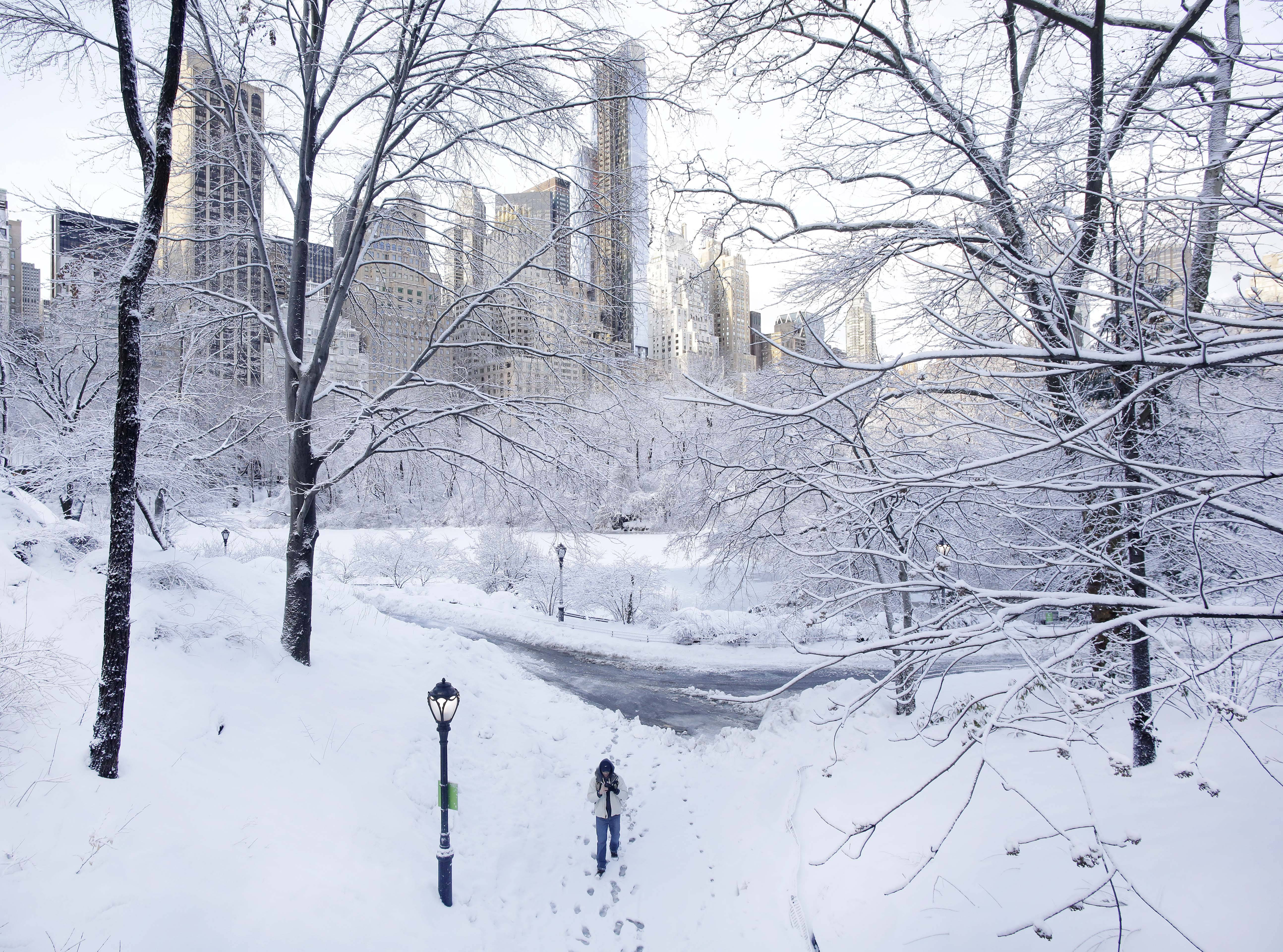 A photographer walks along a snow-covered path in Central Park, Friday, Feb. 14, 2014 in New York. Yet another winter storm brought snow and ice to the East Coast.