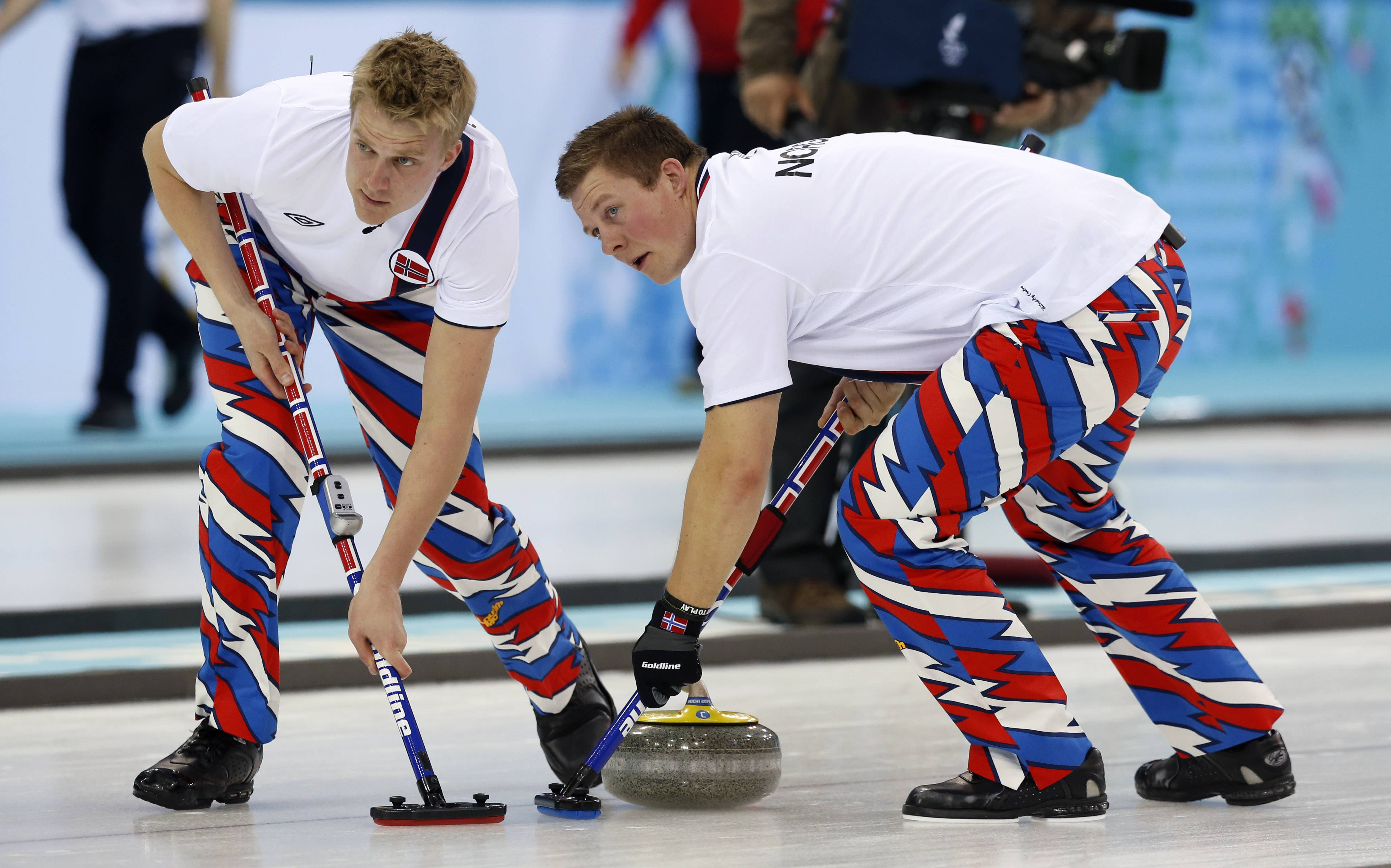 Haavard Vad Petersson, left, and Christoffer Svae sweep ahead of the stone during men's curling competition against China.