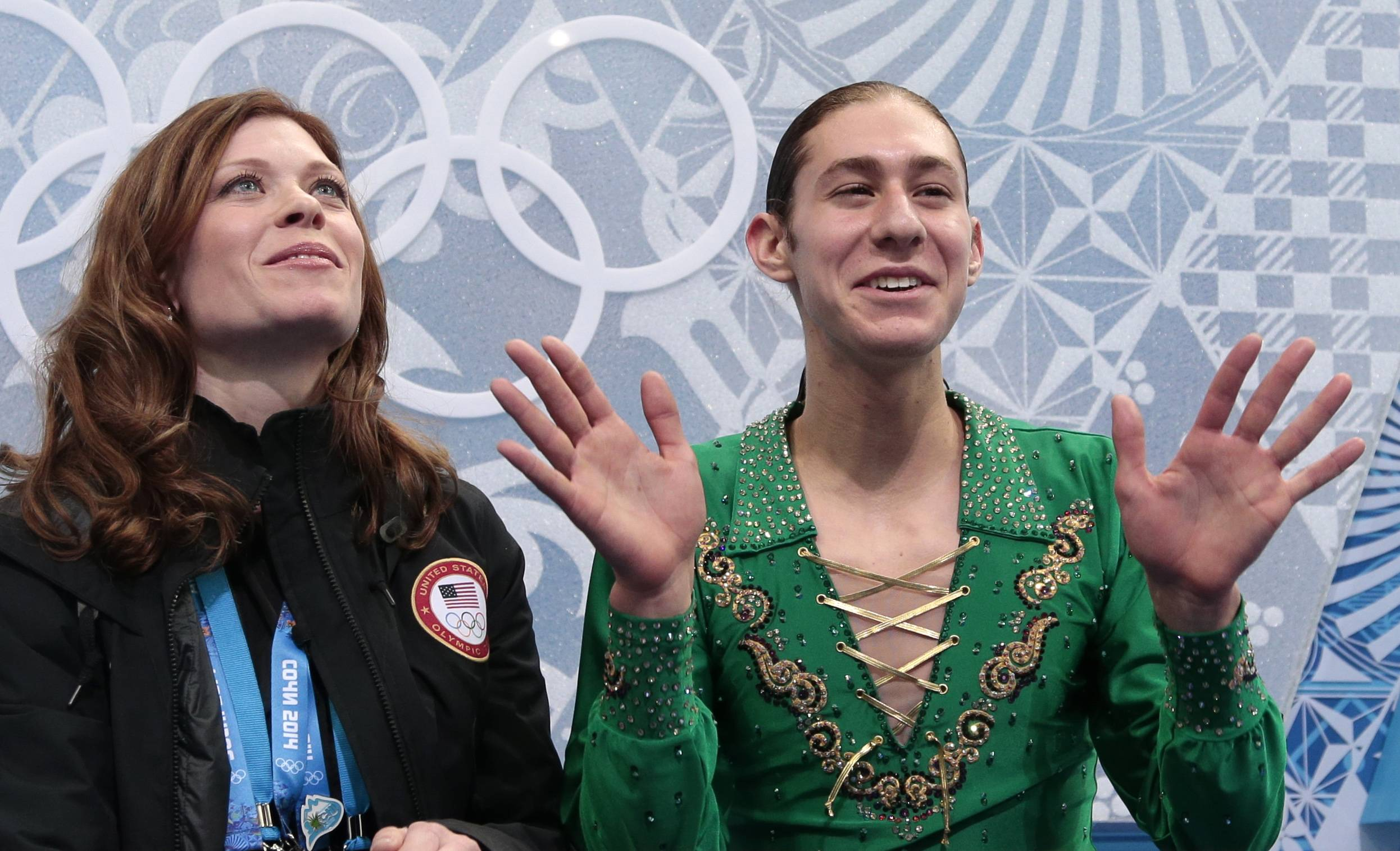 Jason Brown of the United States, left, waves to spectators as he waits in the results area alongside his coach Kori Ade after the men's free skate figure skating final.