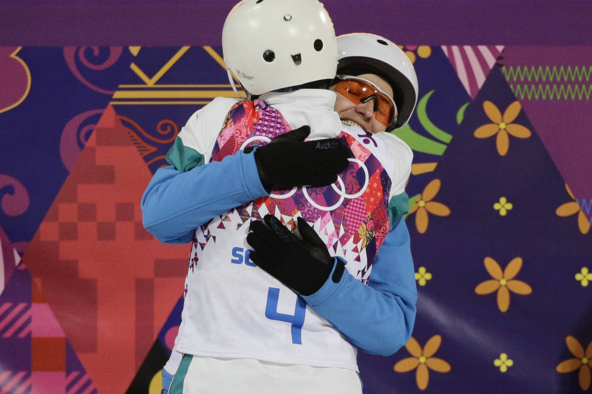 Women's freestyle skiing aerials gold medalist Alla Tsuper, facing camera, of Belarus, is hugged by bronze medalist Lydia Lassila, of Australia.