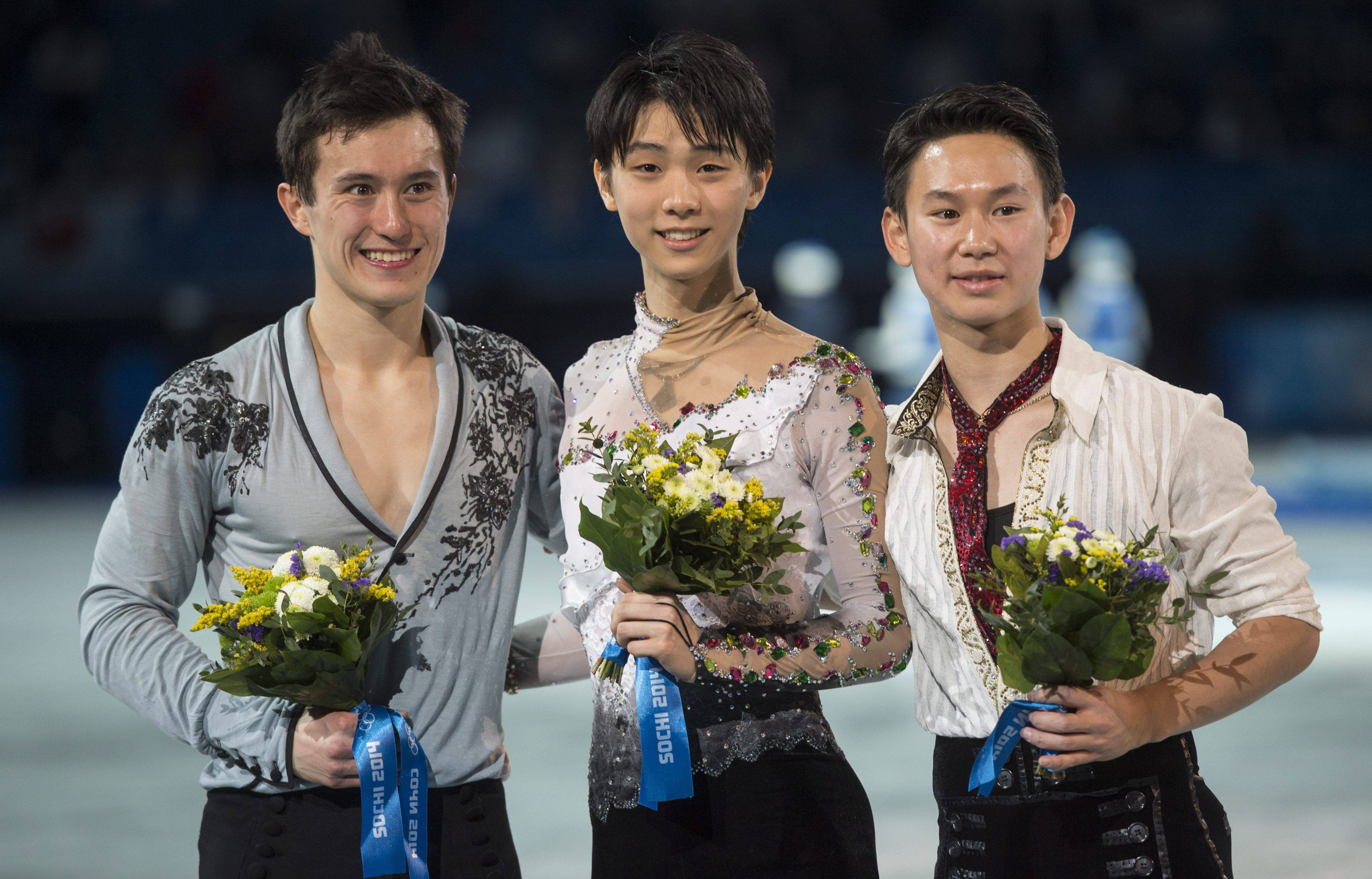 Gold medalist Yuzuru Hanyu of Japan, center, silver medalist Patrick Chan of Canada, left, and bronze medalist Denis Ten of Kazakhstan, pose for photographs on the podium during the flower ceremony after the men's free skate figure skating final.