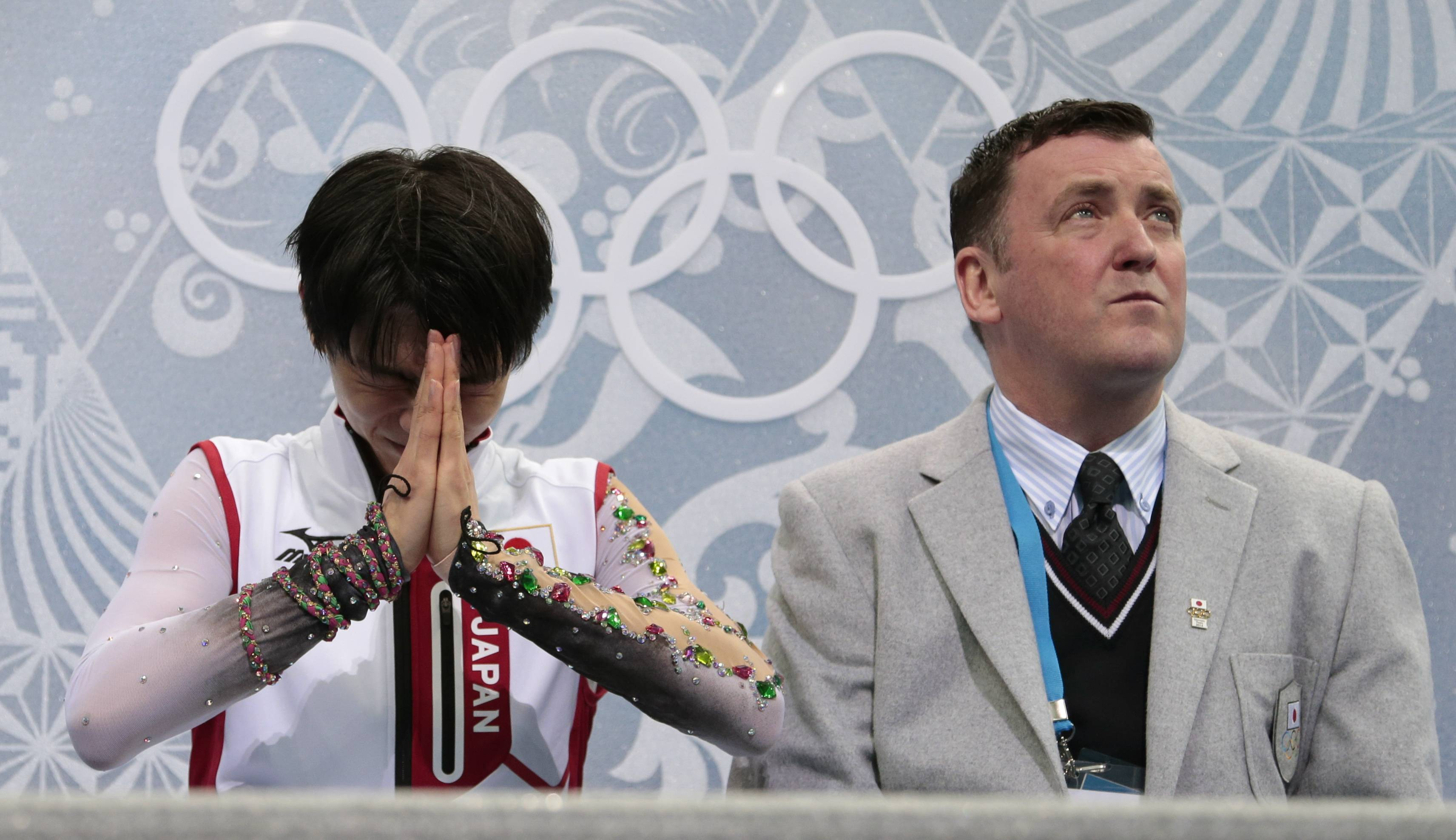 Yuzuru Hanyu of Japan, left, reacts alongside his coach Brian Orser as he sits in the results area after the men's free skate figure skating final.
