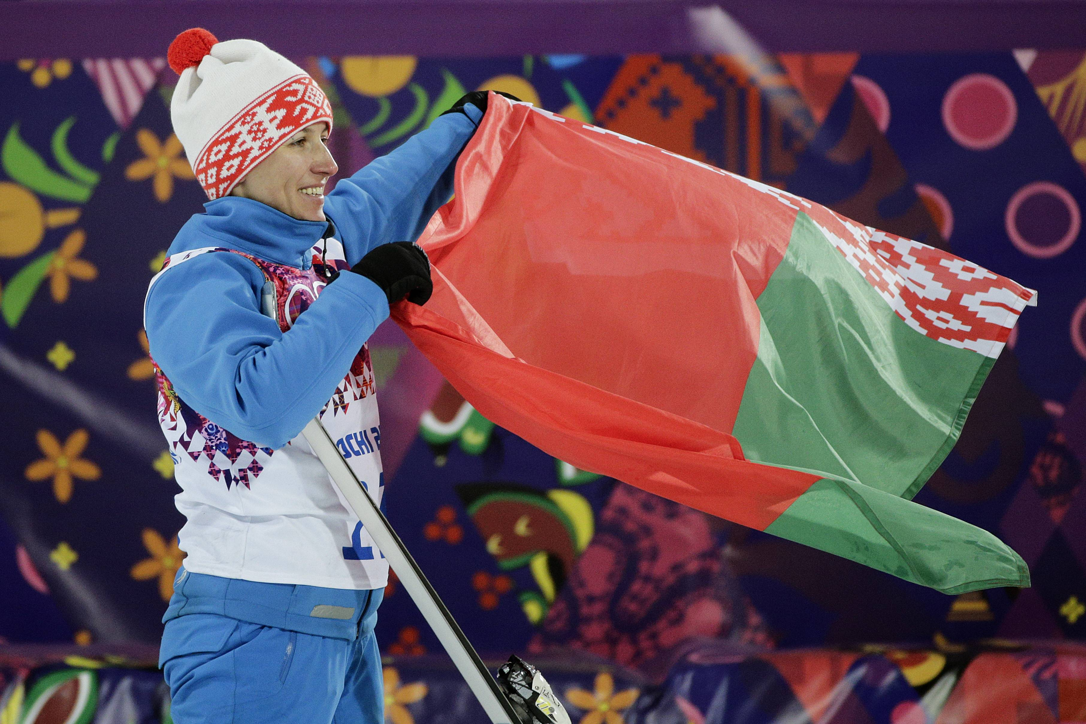 Gold medalist Alla Tsuper, of Belarus, poses with a Belarusian flag after a flower ceremony for the women's freestyle skiing aerials final.