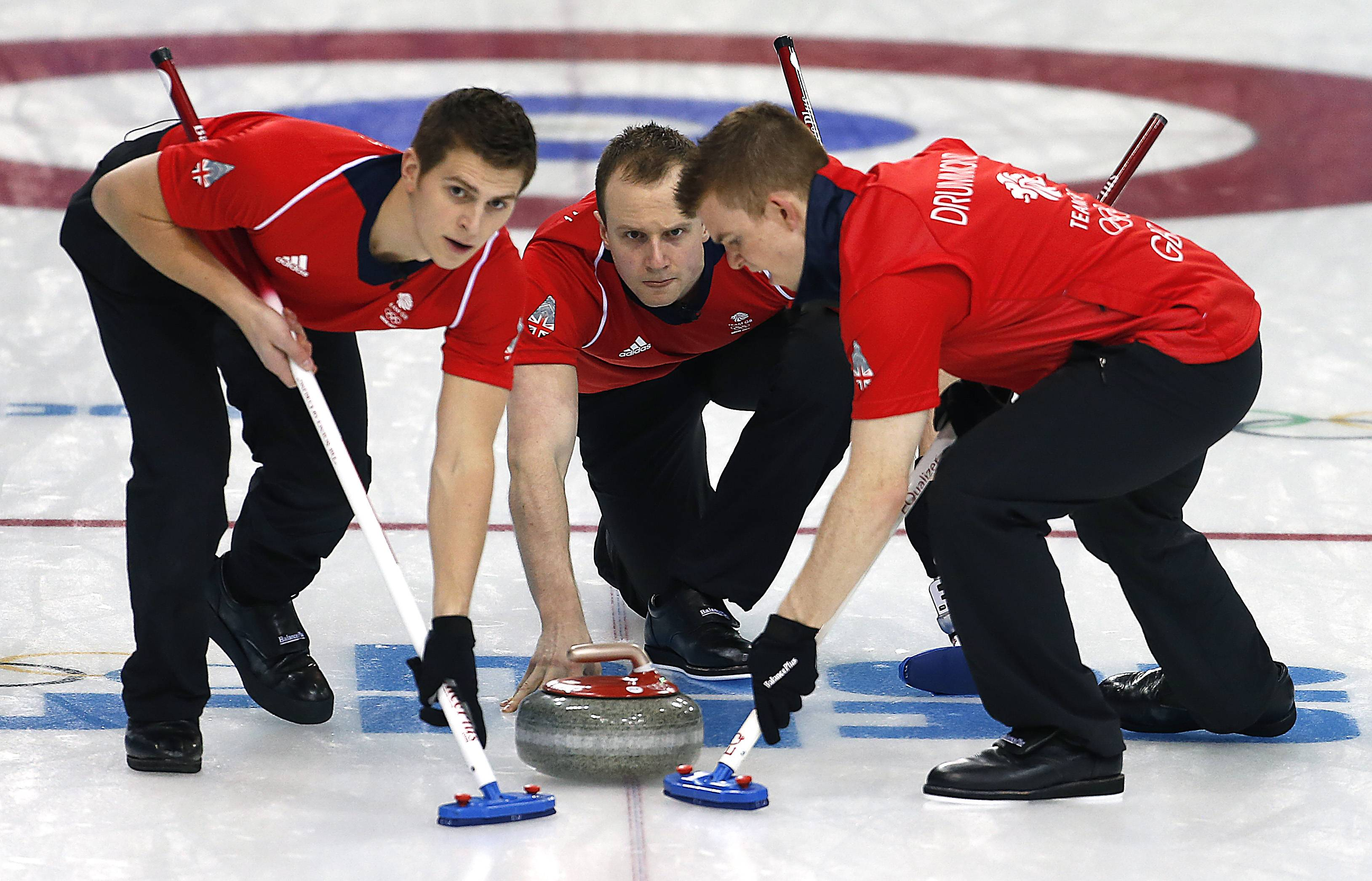 Britain's Michael Goodfellow, center, releases the rock while Scott Andrews, left, and Greg Drummond, right, sweep the ice during the men's curling competition against Denmark.