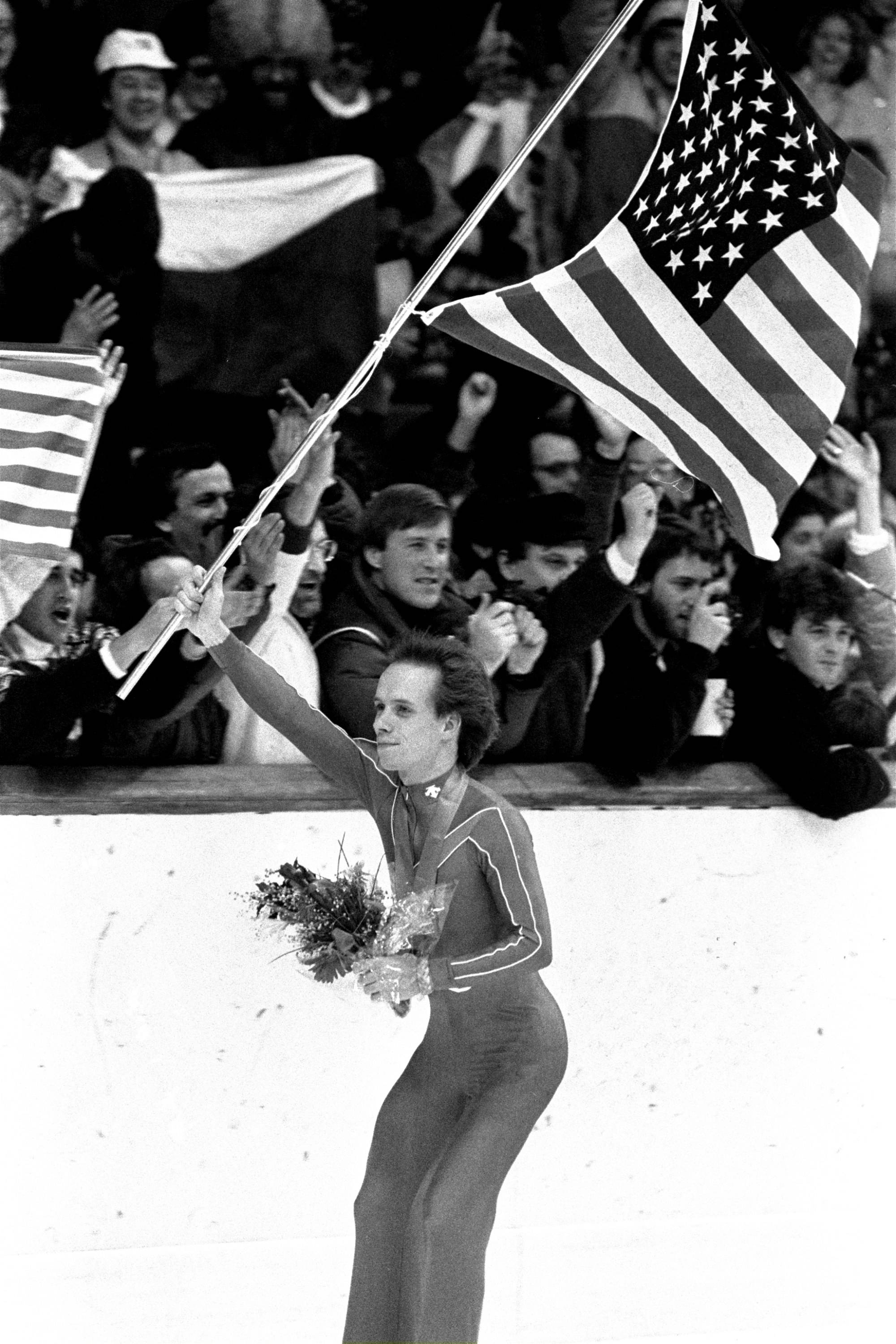Figure skater Scott Hamilton of the United States carries an American flag past a cheering crowd after he was awarded a gold medal in figure skating at the 1984 Winter Games at Zetra's ice rink in Sarajevo.