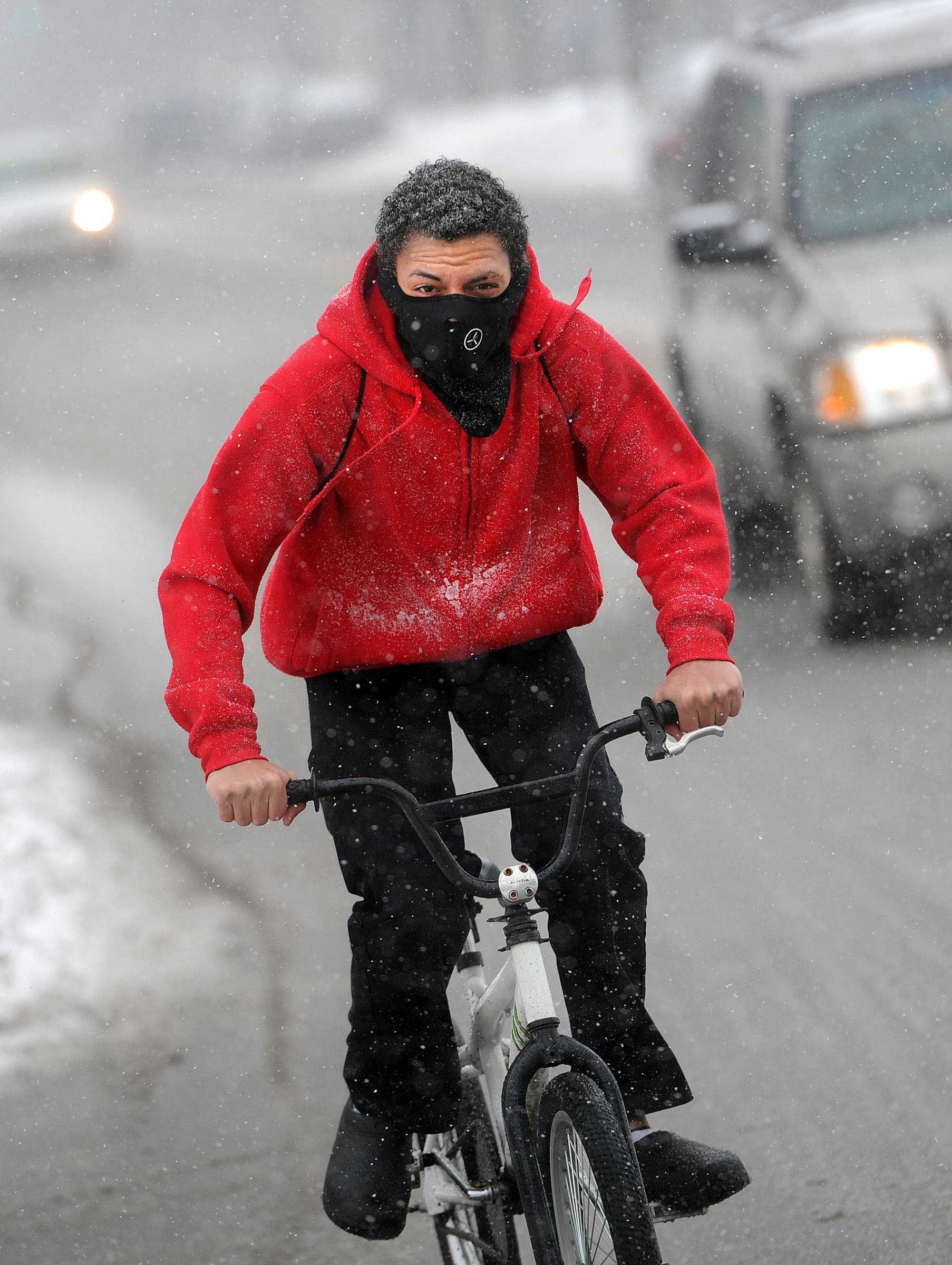 Emanuel Comfort, 17, rides his bike Saturday in the snowfall on South George Street in York, Pa.