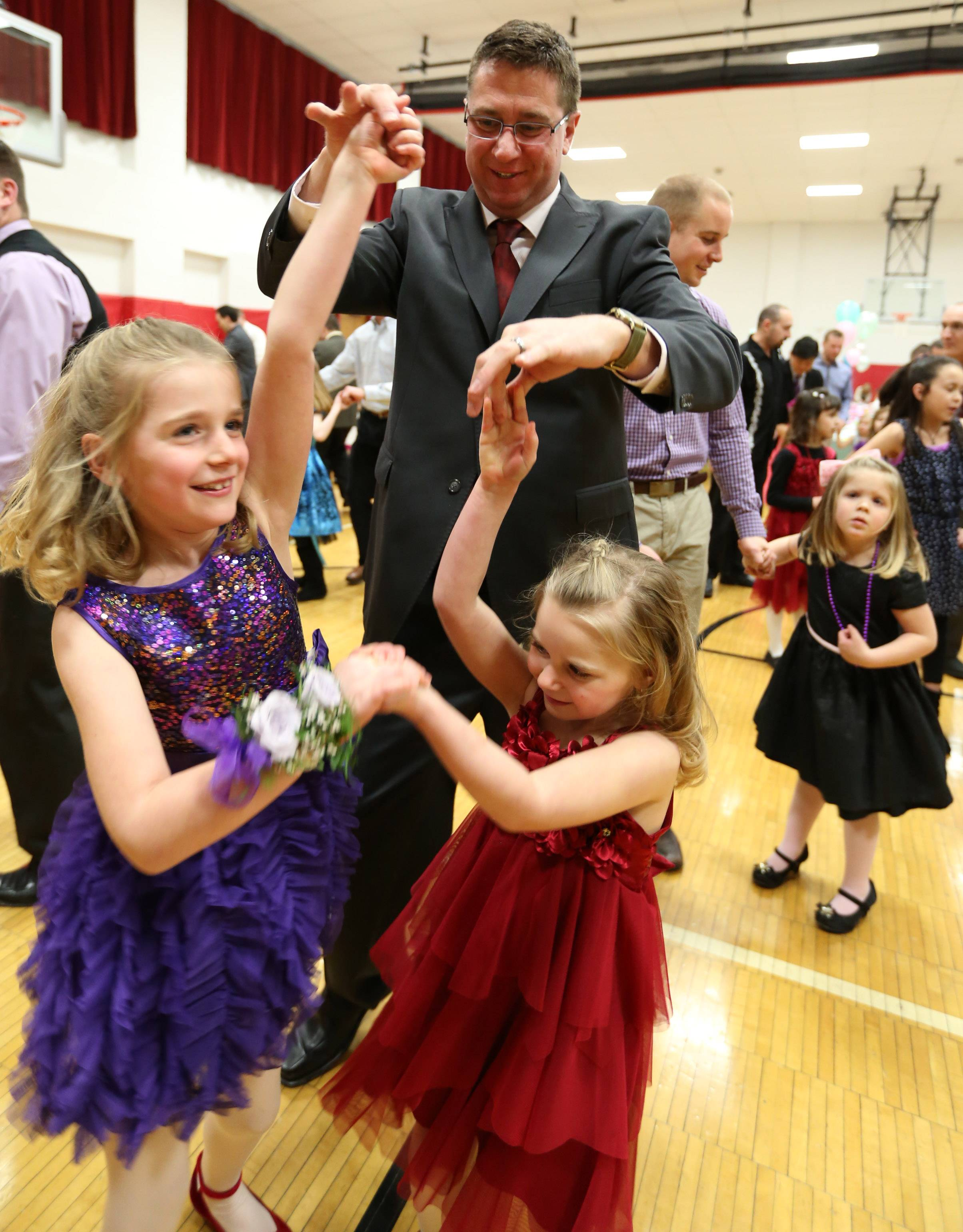 Rob Kaergard of Schaumburg dances with his two daughters Brooke, 7, left, and Kira, 5, at a dad and daughter dance at the Community Recreation Center on Saturday night in Schaumburg.